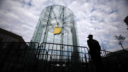 A security guard stands next to an Apple retail store during the release of the iPhone 5 in Shanghai