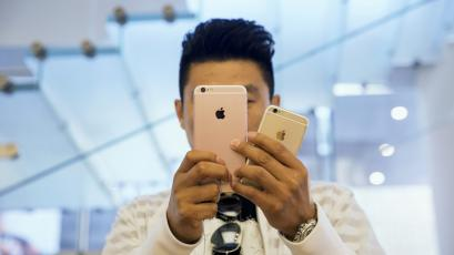 A man takes pictures as Apple iPhone 6s and 6s Plus go on sale at an Apple Store in Beijing