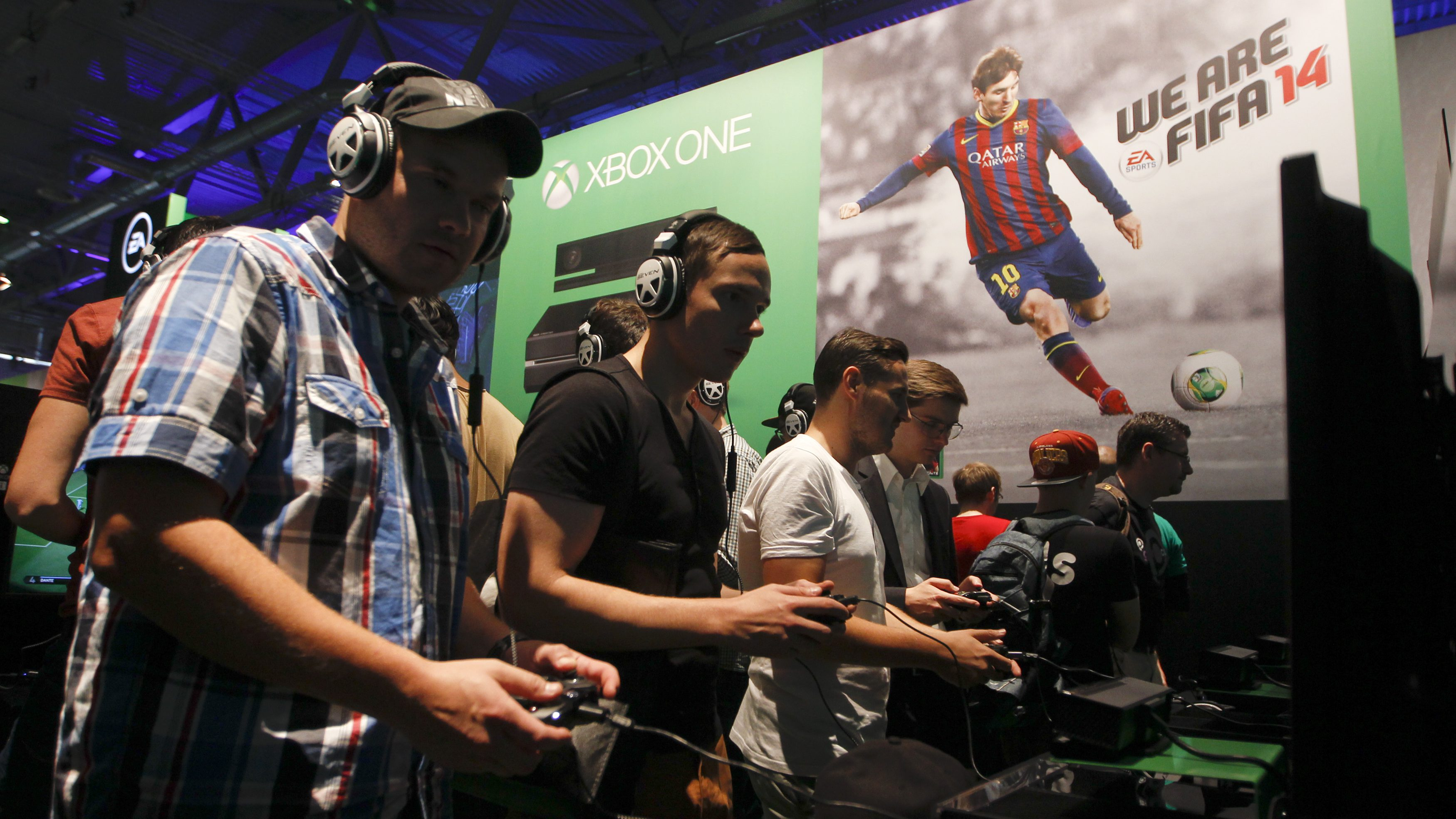 """Visitors play """"FIFA 14"""" with the Xbox One at the Microsoft Games exhibition stand during the Gamescom 2013 fair in Cologne"""