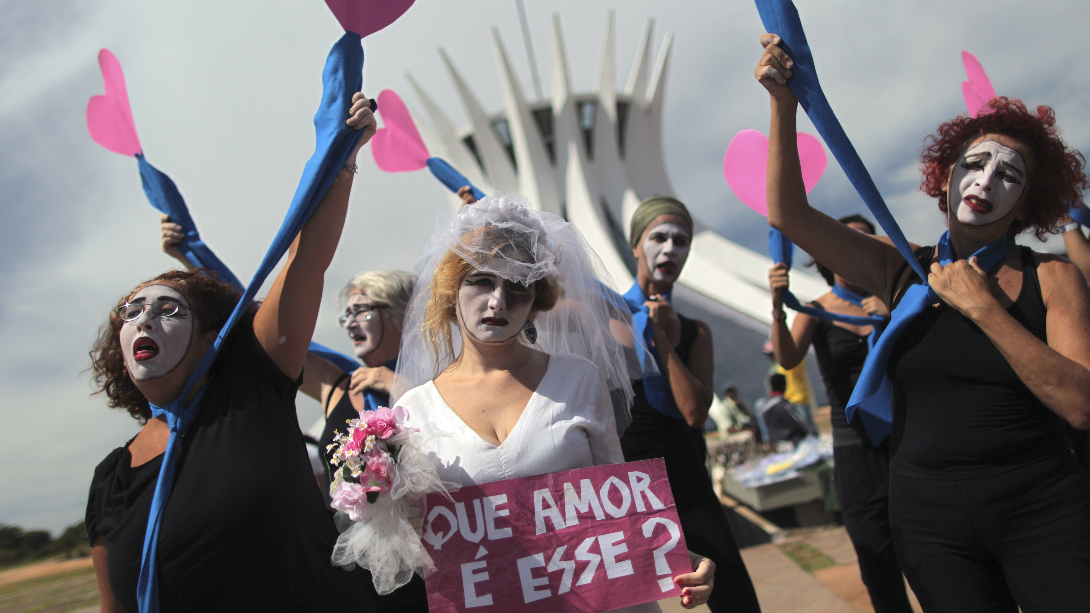 "Women hold up heart-shaped pieces of paper as they protest about violence against women, at the close of the National Meeting of Rural Women, in Brasilia February 21, 2013. The sign reads, ""What love is this?"" REUTERS/Ueslei Marcelino (BRAZIL - Tags: POLITICS CIVIL UNREST TPX IMAGES OF THE DAY)"