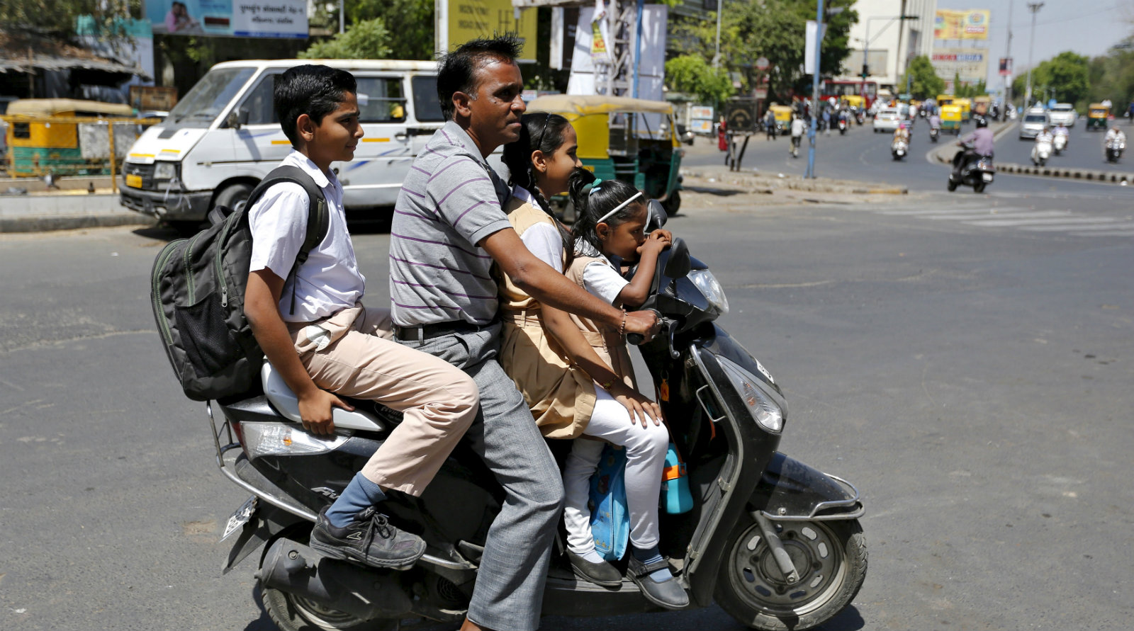 A man rides a scooter and ferries students to their school in Ahmedabad, India, March 22, 2016.