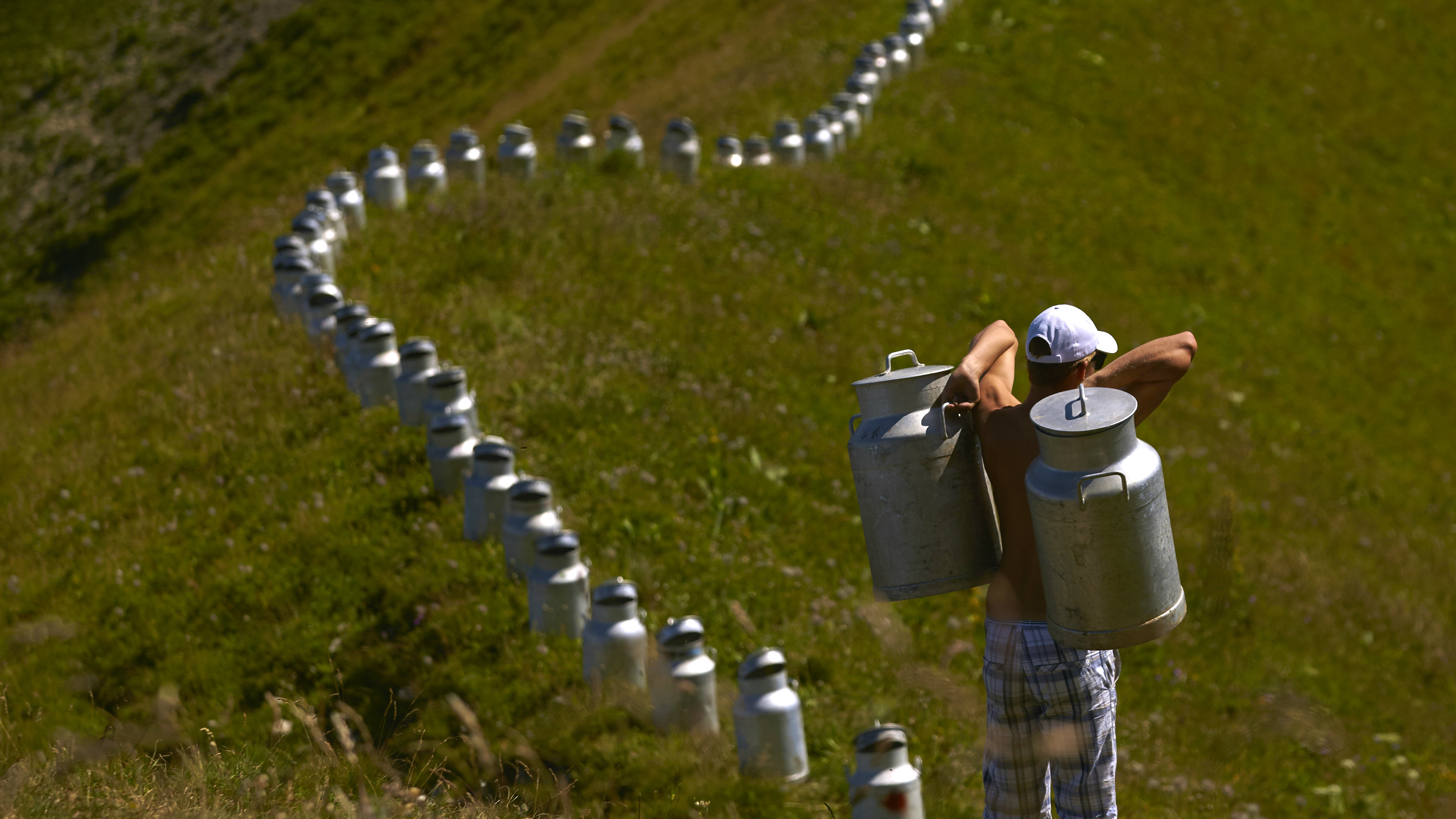"""A volunteer carries milk churns as he helps land art artist Gerard Benoit a la Guillaume to form an art installation at the Chenau de Mayen in the resort of Leysin, Switzerland August 7, 2015. More than 80 milk churns were placed between the Tour d'Ai and the Tour de Mayen summits at an altitude of 2,000 meters (6,561 feet) above sea level under the direction of the artist, to be photographed for his ongoing art project entitled """"Milk churns without borders"""". REUTERS/Denis Balibouse"""