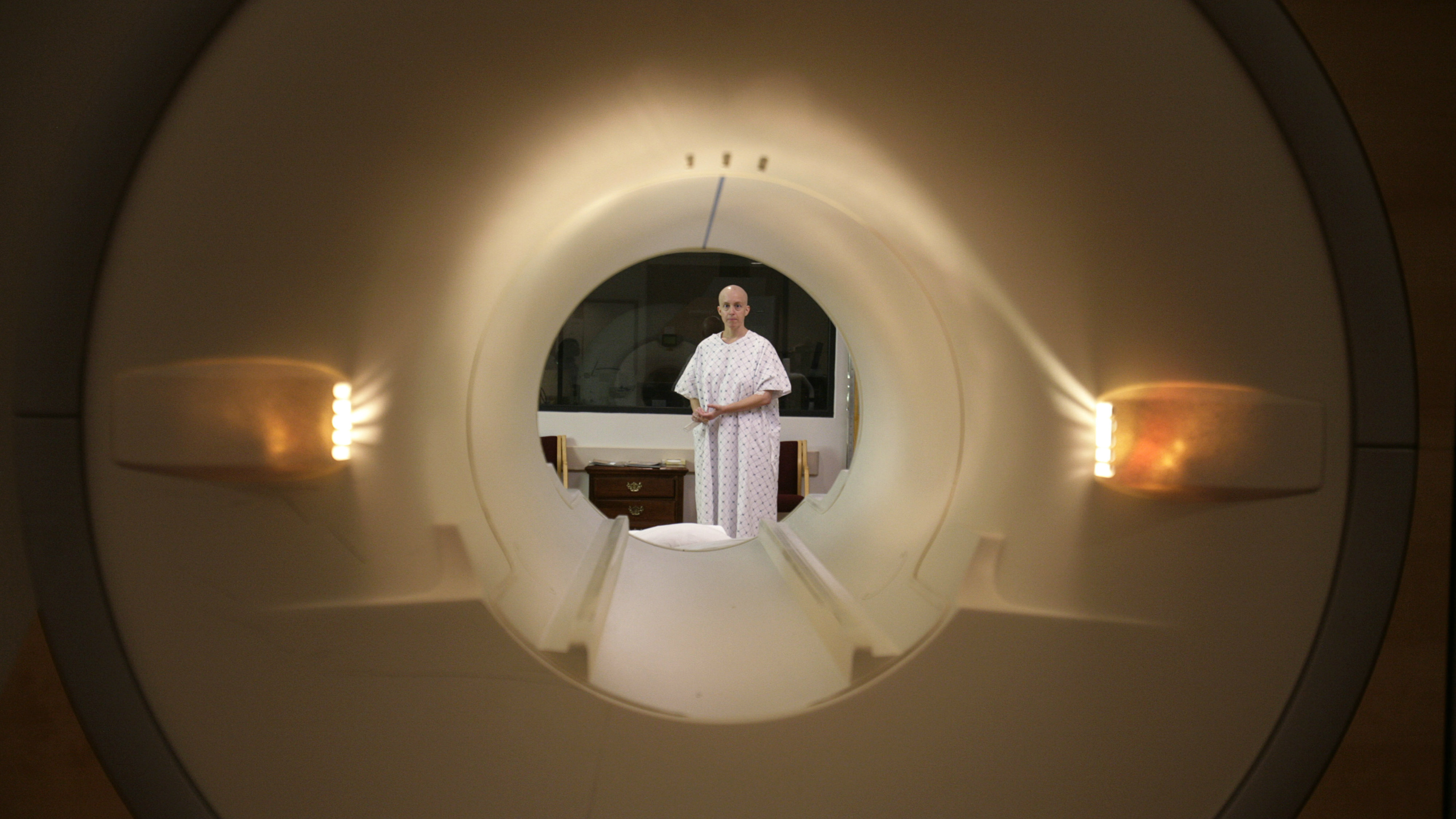 Cancer patient Deborah Charles is seen through the tube of a magnetic resonance imaging scanner as she prepares to enter the MRI machine for an examination at Georgetown University Hospital in Washington May 23, 2007. Like many cancer patients, Charles now spends many of her days going for medical appointments, treatments and examinations. Photo taken May 23, 2007.