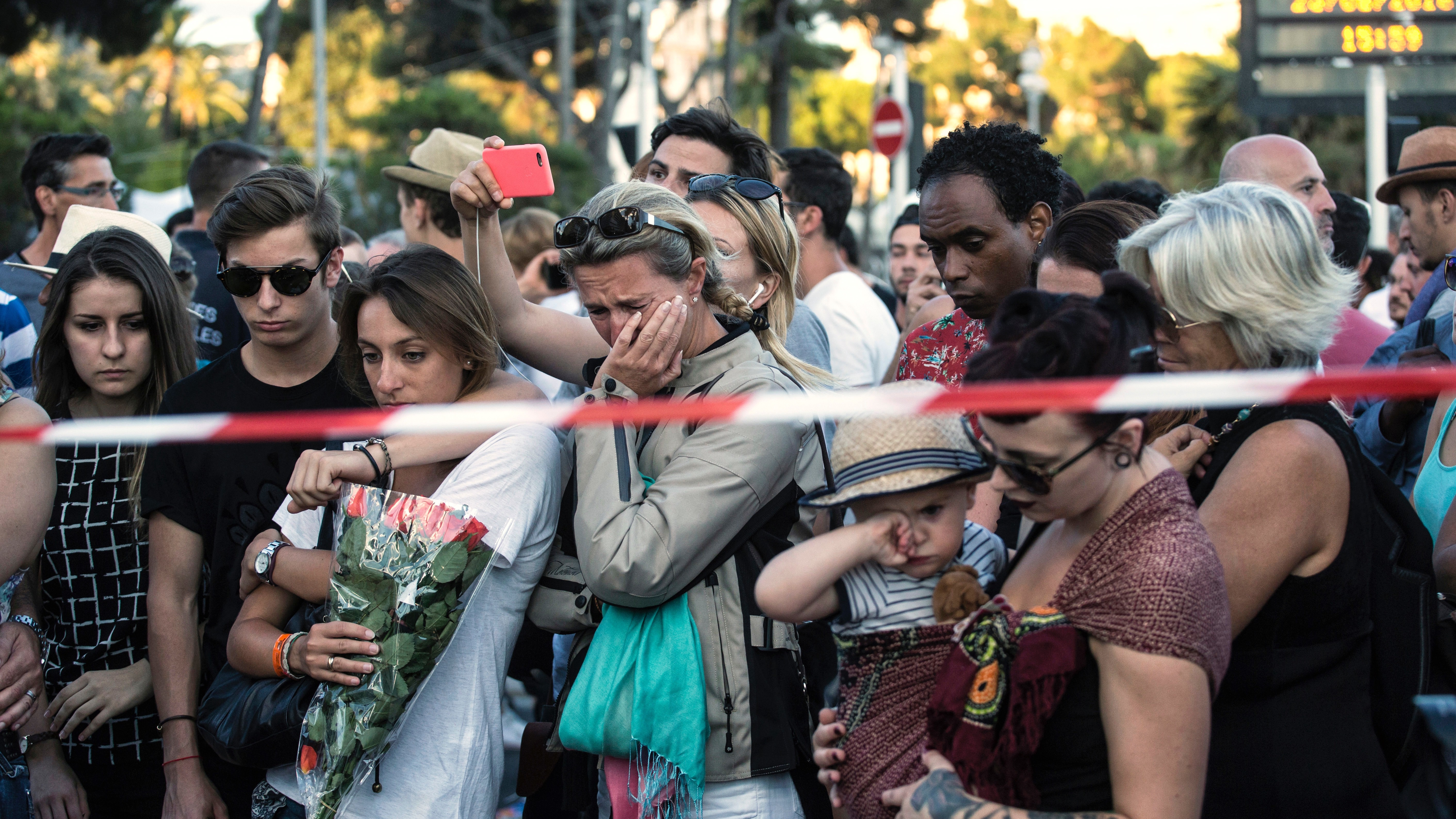 """""""People react as they gather at a makeshift memorial to honor the victims of an attack near the area where a truck mowed through revelers in Nice, southern France, Friday, July 15, 2016. A large truck mowed through revelers gathered for Bastille Day fireworks in Nice, killing more than 80 people and sending people fleeing into the sea as it bore down for more than a mile along the Riviera city's famed waterfront promenade. (AP Photo/Laurent Cipriani)"""
