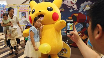 A girl poses with Pikachu for photos during a Pokemon festival in Tokyo, Monday, July 18, 2016. The summer event marking the release of the latest movie of Pokemon is held until the end of August. (AP Photo/Koji Sasahara)