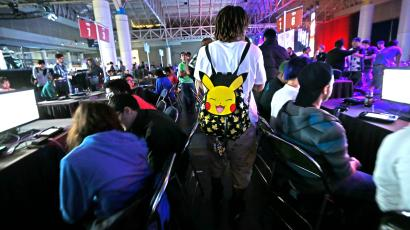 A visitor with a Pokemon backpack walks through a gaming area at the Major League Gaming World Finals in New Orleans, Friday, Oct. 16, 2015. Thousands of people are converging on New Orleans this weekend for the tournament. Players from around the world are competing in such games as Call of Duty: Advanced Warfare and Dota 2. The event started Friday and goes through Sunday at the convention center. (AP Photo/Gerald Herbert)