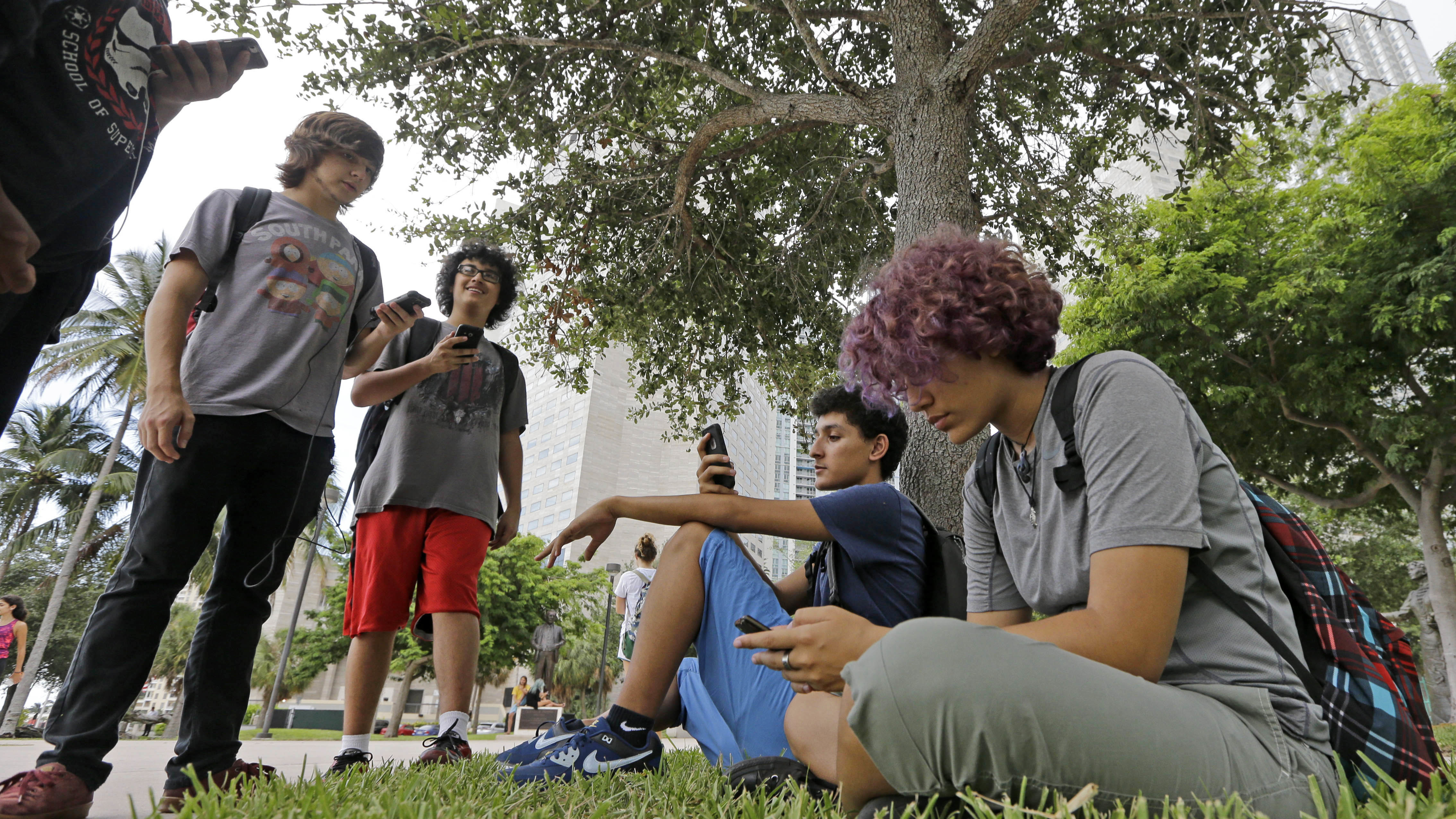 """Pokemon Go players Ana Valentina Ojeda, right, and Jaeden Valdespino, second from right, check their smartphones as they look for Pokemon, Tuesday, July 12, 2016, at Bayfront Park in downtown Miami. The """"Pokemon Go"""" craze has sent legions of players hiking around cities and battling with """"pocket monsters"""" on their smartphones. (AP Photo/Alan Diaz)"""