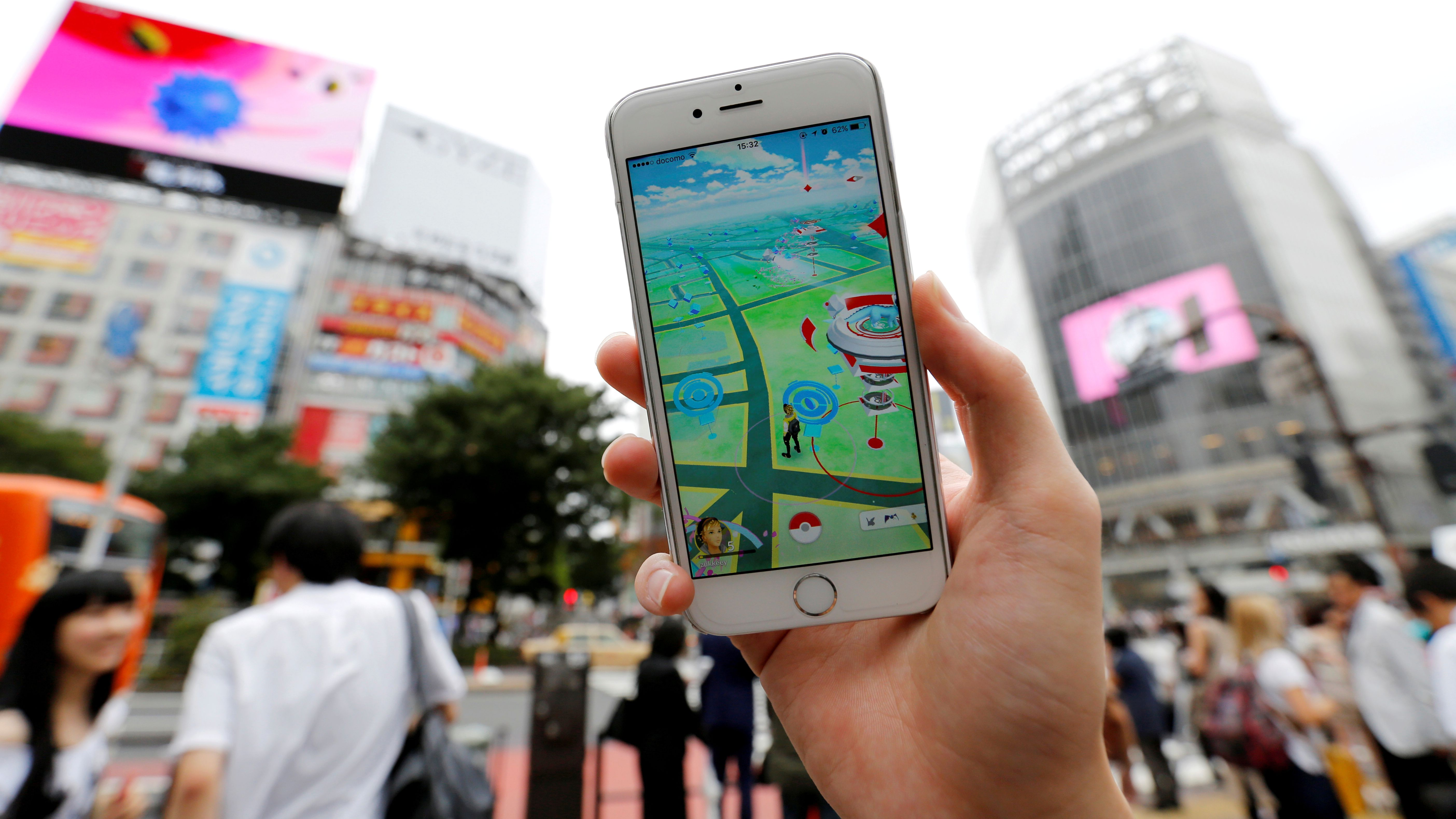 """A man poses with his mobile phone displaying the augmented reality mobile game """"Pokemon Go"""" by Nintendo in front of a busy crossing in Shibuya district in Tokyo, Japan, July 22, 2016."""