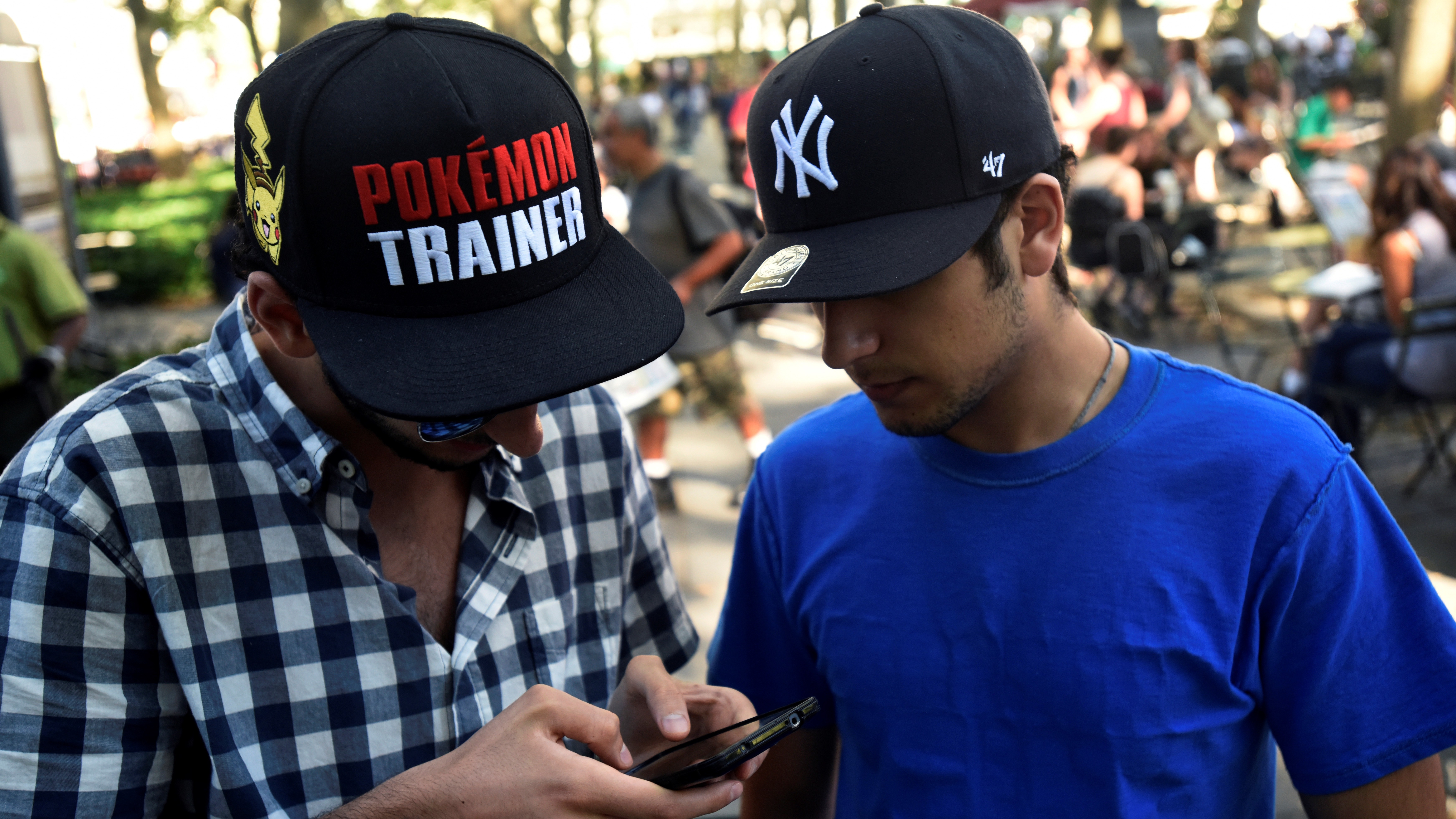 """A man wears a Pokemon-themed hat as he plays the augmented reality mobile game """"Pokemon Go"""" by Nintendo in Bryant Park, New York City, U.S. July 11, 2016. REUTERS/Mark Kauzlarich - RTSHH1S"""