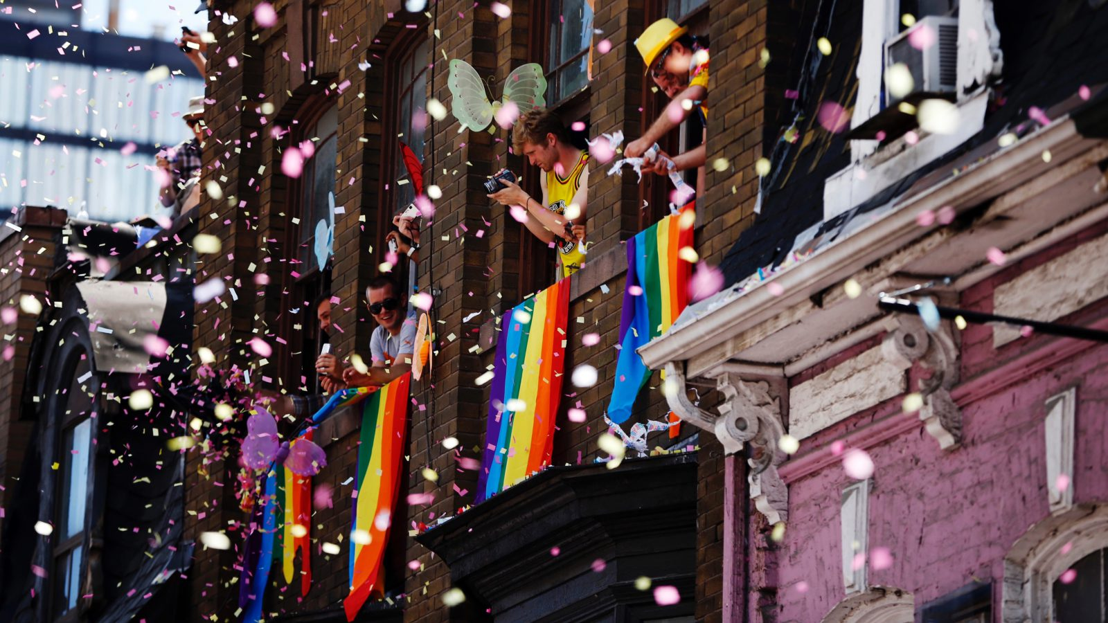 People throw confetti from their windows during the Gay Pride parade in Toronto July 1, 2012.    REUTERS/Mark Blinch (CANADA - Tags: SOCIETY TPX IMAGES OF THE DAY) - RTR34H46