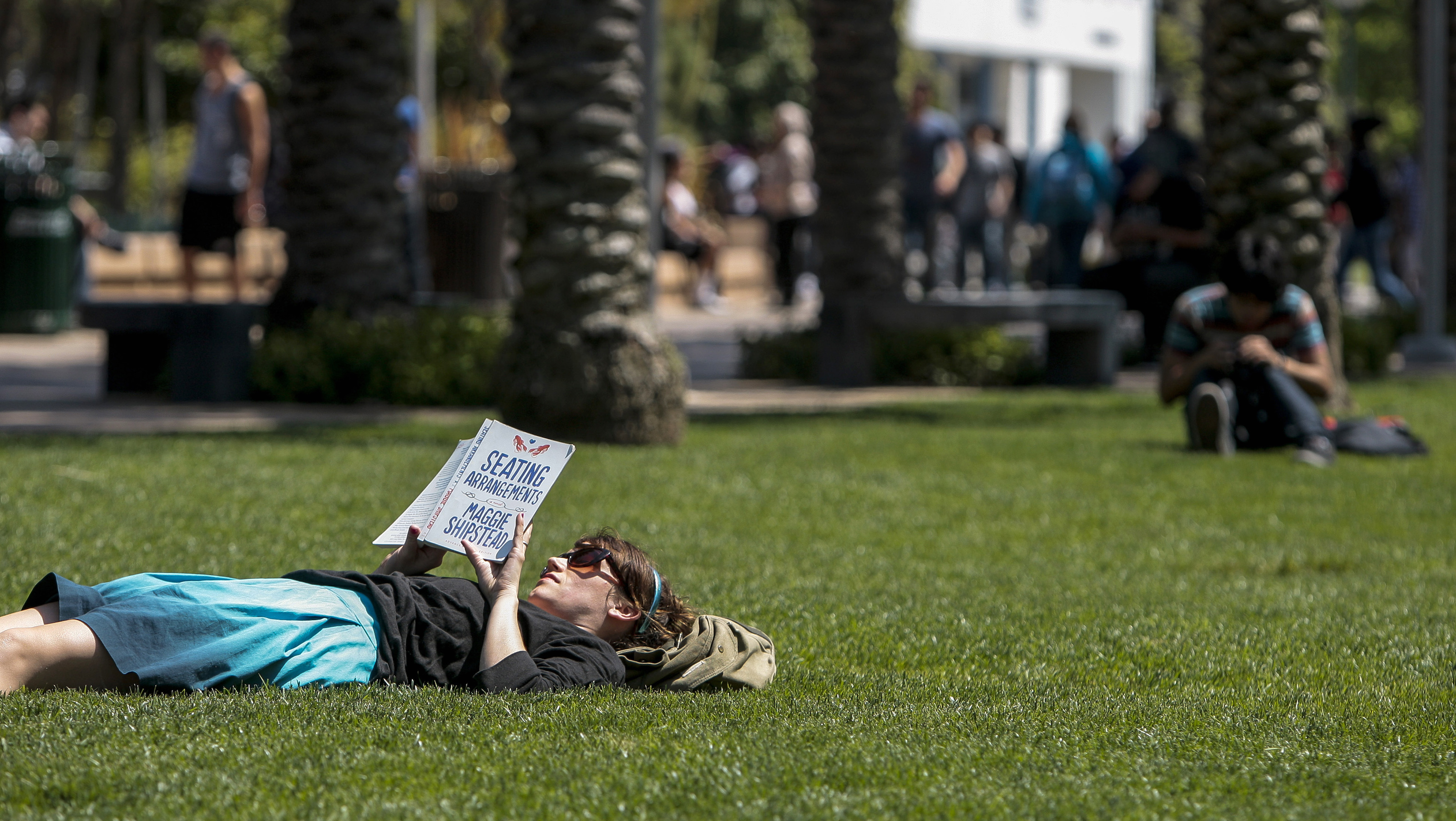 Santa Monica College English Department Assistant Ginger Pennington reads a book while lying on the lawn at Santa Monica College in Santa Monica, California April 4, 2012. The president of the California college defended on Wednesday the use of pepper spray by campus police against students protesting higher tuition for extra summer-school classes, an incident that left as many as 30 people overcome by the caustic substance. REUTERS/Bret Hartman  (UNITED STATES - Tags: EDUCATION CIVIL UNREST POLITICS) - RTR30CPM