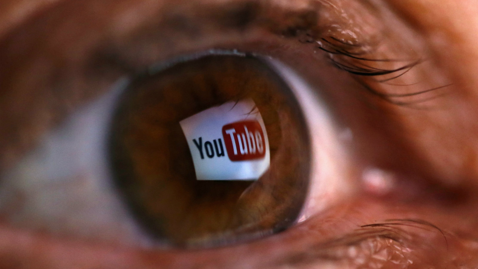 "A picture illustration shows a YouTube logo reflected in a person's eye, in central Bosnian town of Zenica, early June 18, 2014. Google Inc's YouTube said on June 17, 2014 that it plans to launch a paid streaming music service, amid criticism that its existing, free video website might block the music videos of labels that do not agree to its terms. YouTube has partnered with ""hundreds of major and independent"" music labels for the new service, the company said in a statement, confirming long-running rumors that the world's most popular online video website will offer a paid music service. The picture was flipped horizontally."
