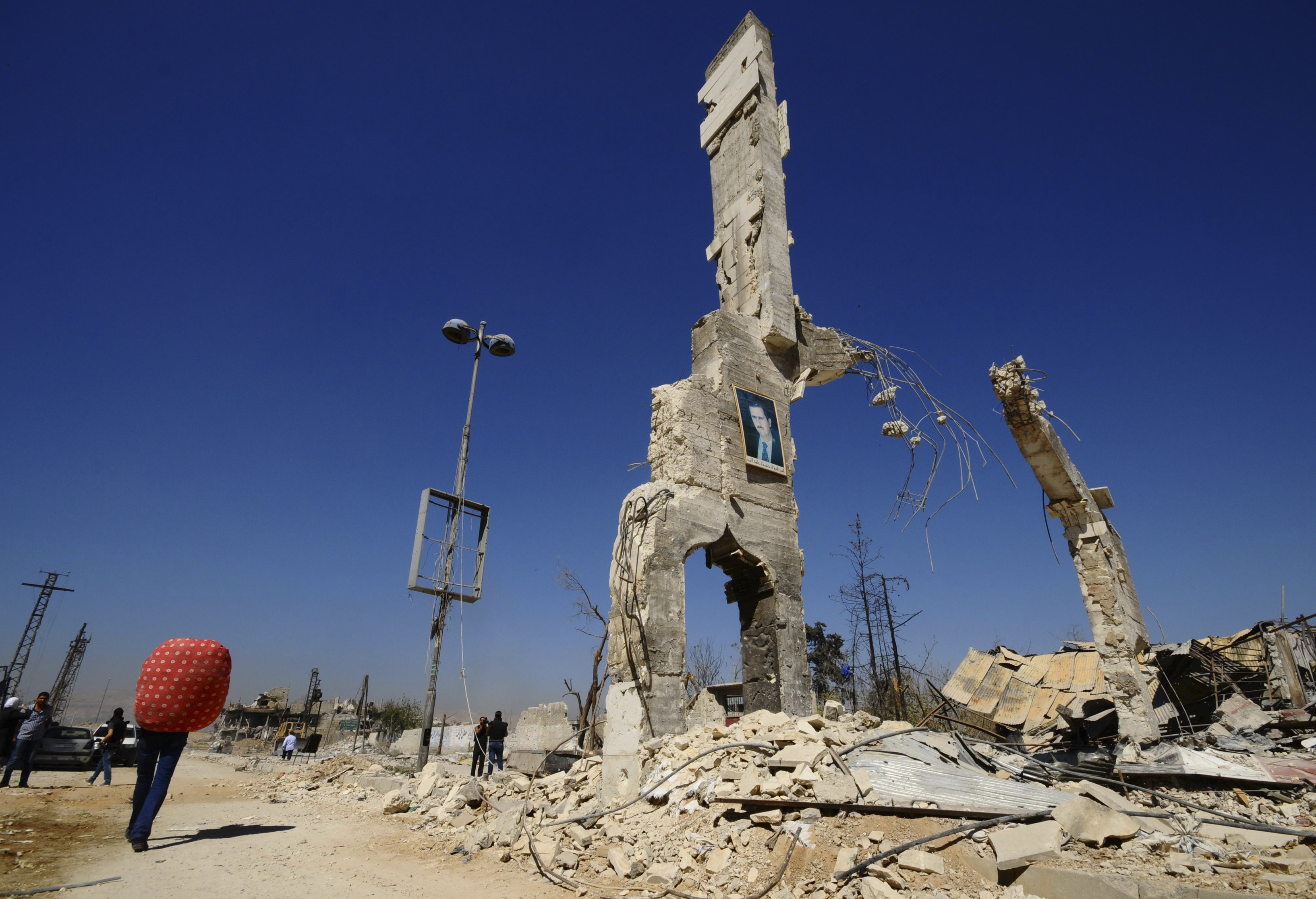A picture of Syria's President Assad is displayed on a damaged structure at the entrance of al-Dukhaneya neighbourhood near Damascus