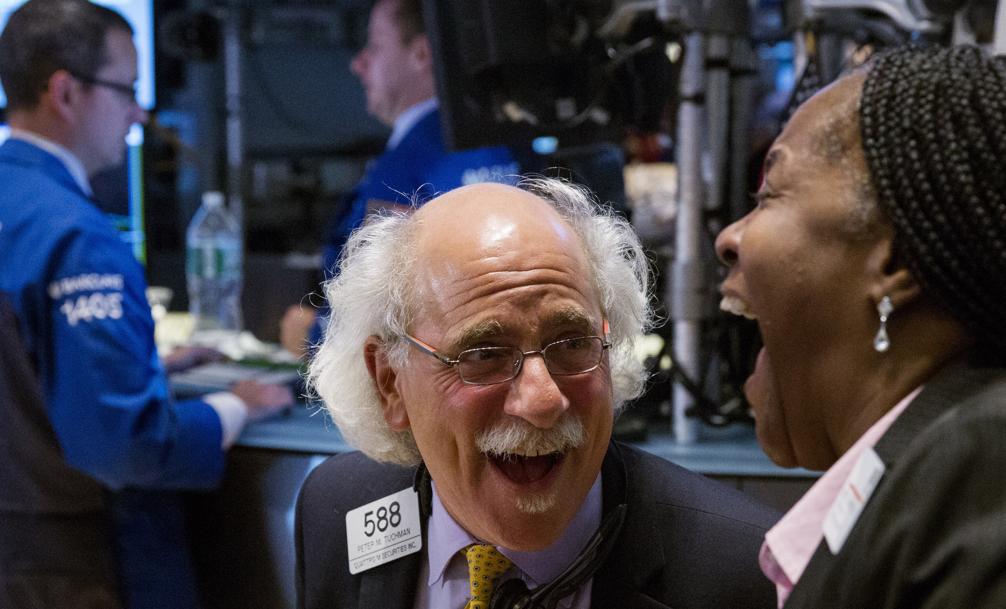 Traders laugh as they work on the floor of the New York Stock Exchange as the market closes in New York October 17, 2014.