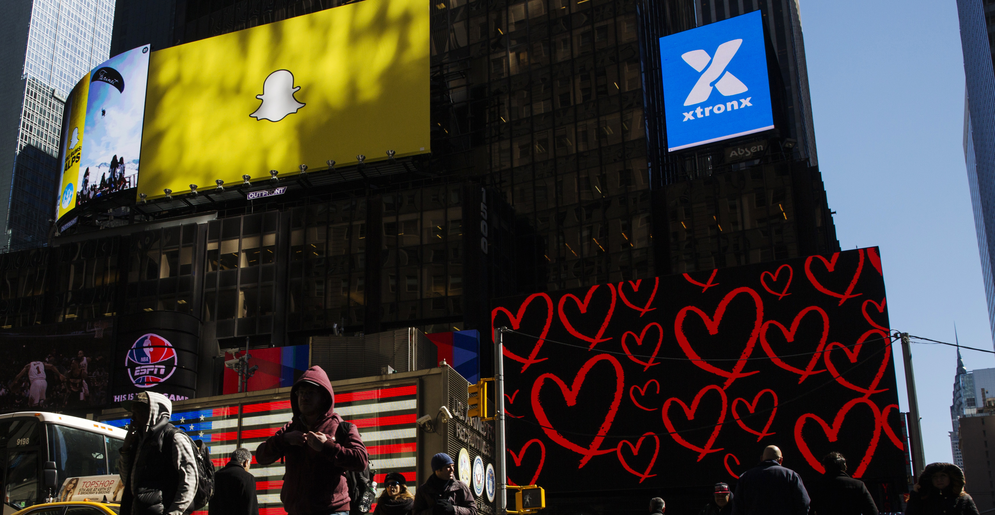 Pedestrians cross the street below a billboard displaying the logo of Snapchat above Times Square in New York March 12, 2015.