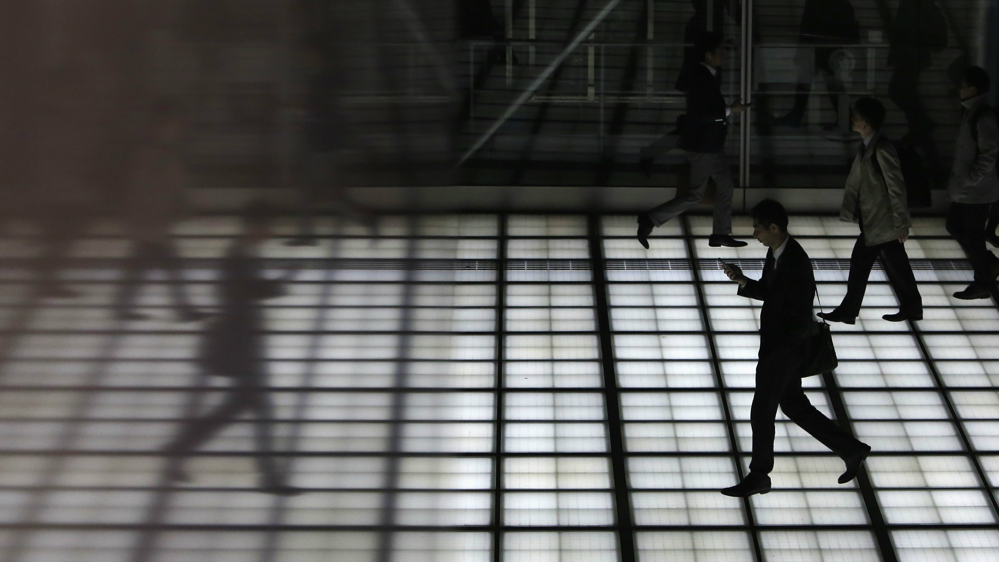 A man with his mobile phone walking is reflected in a wall of a building at Tokyo's business district March 18, 2015.