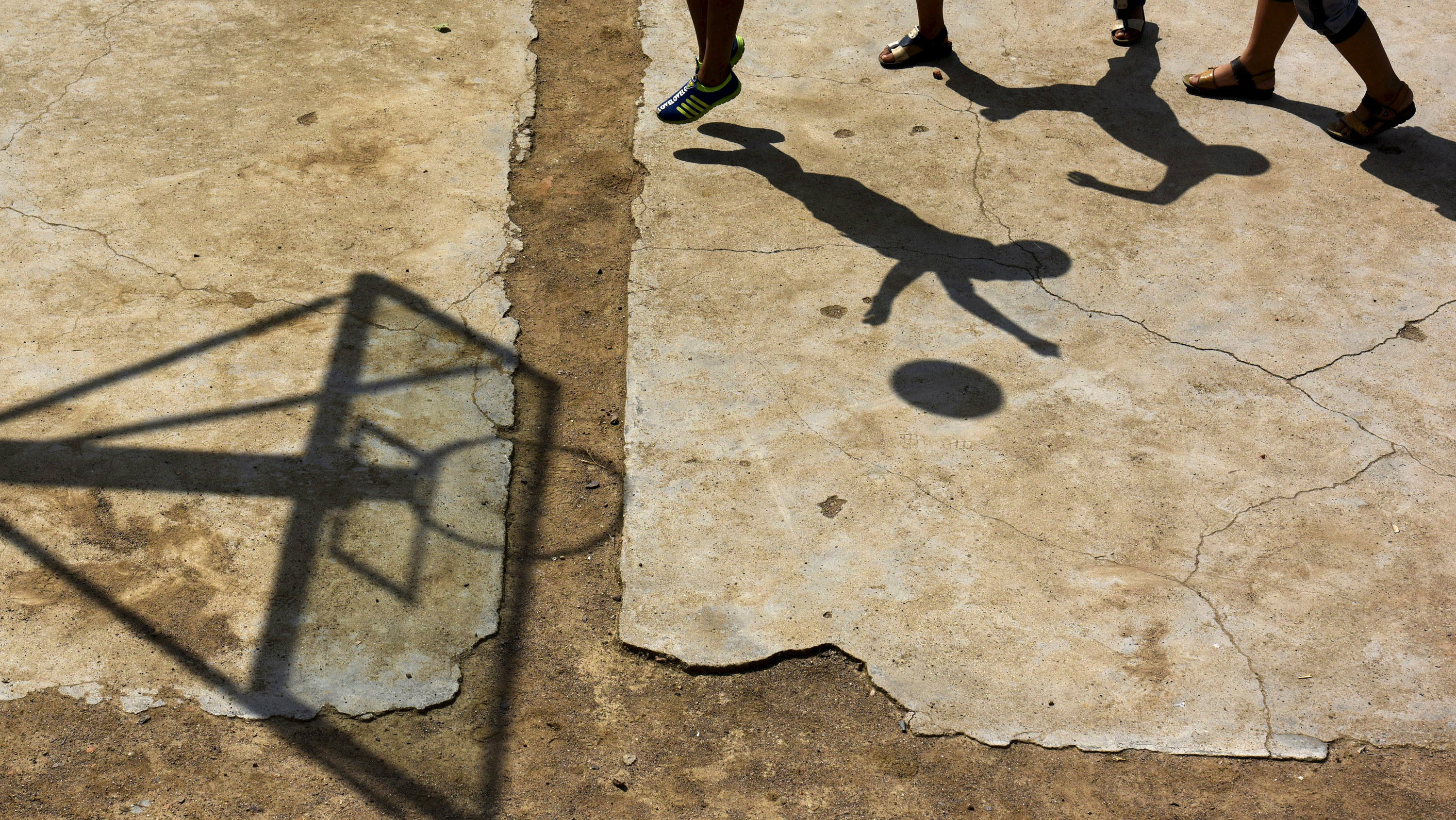 Students cast shadows as they play basketball at a playground at Dalu primary school in Gucheng township of Hefei, Anhui province, China, September 8, 2015.