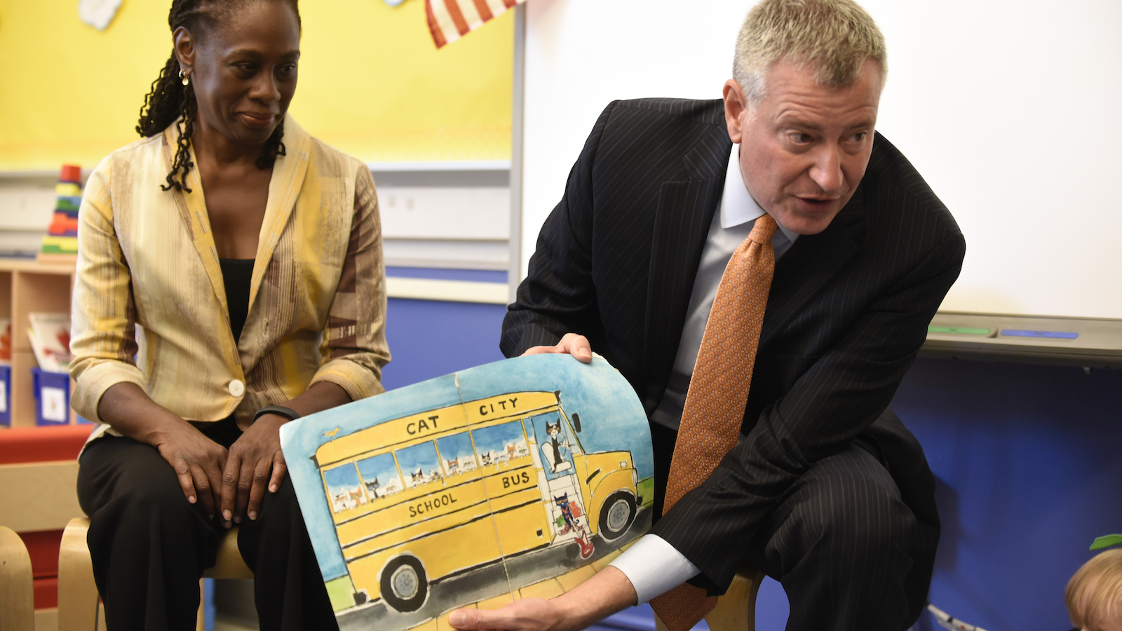 New York City Mayor Bill de Blasio (R) reads a book to pre-K students on their first day of school at Public School 59 in Staten Island, New York, September 9, 2015.  At left is First Lady Chirlane McCray.  REUTERS/Barry Williams/Pool - RTSBSU