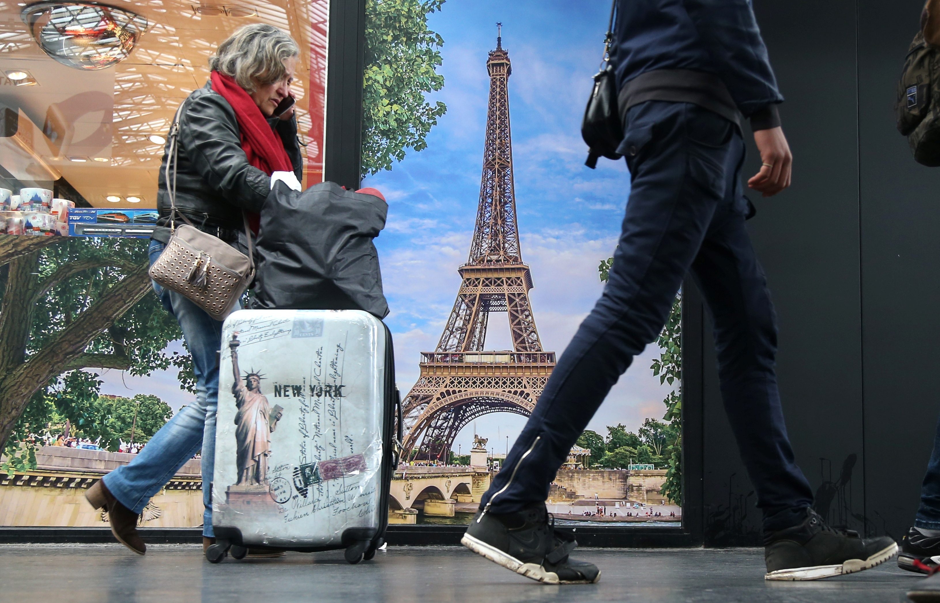 Passengers carry their bags as they pass a poster of the Eiffel tower at Gare de l'Est railway station in Paris
