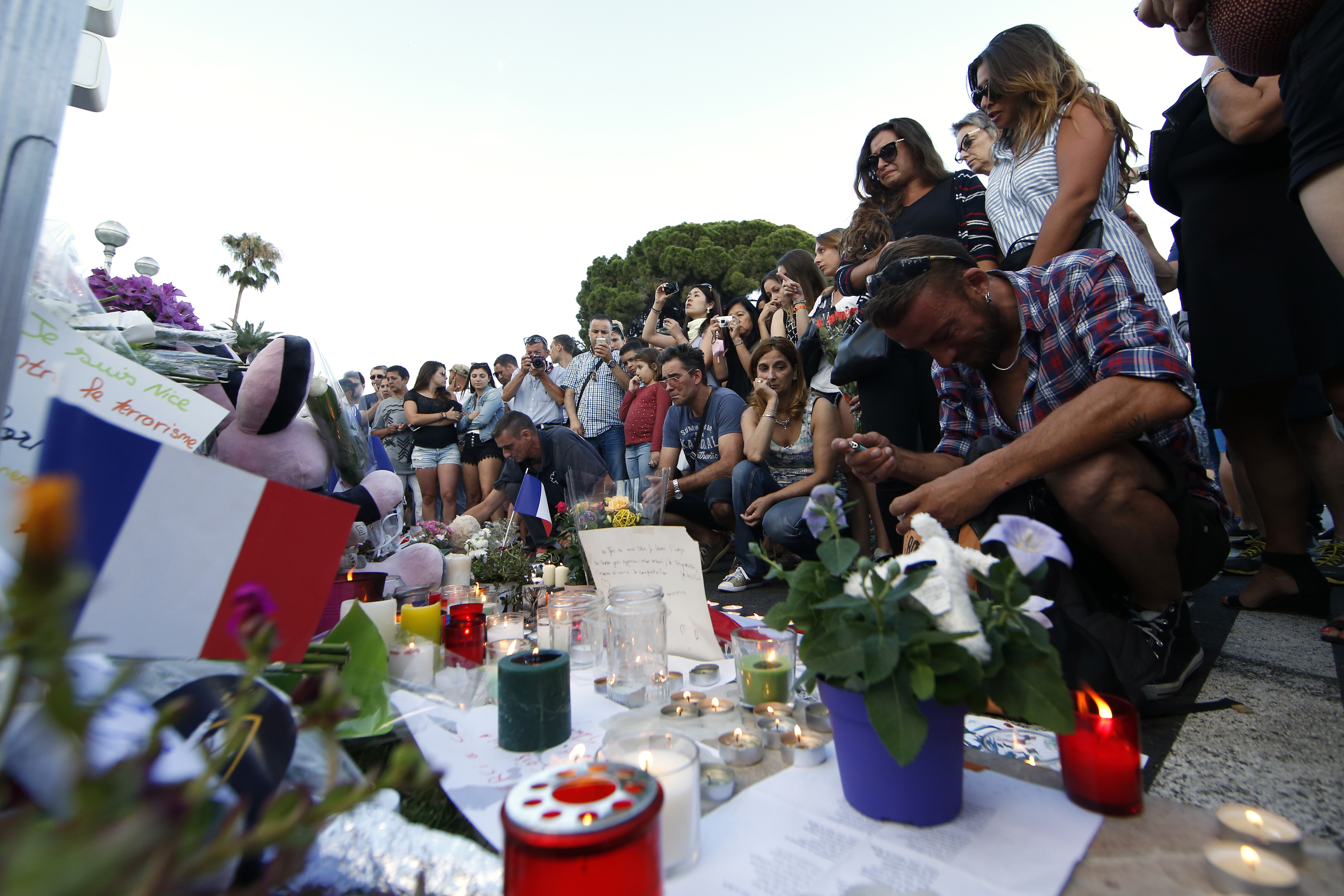People gather near flowers and candles left in tribute to victims the day after a truck ran into a crowd at high speed killing scores and injuring more who were celebrating the Bastille Day national holiday