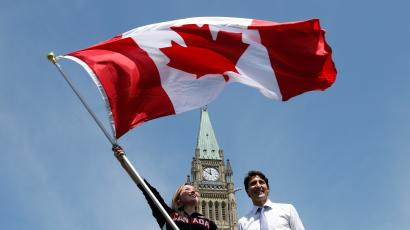 Trampolinist Rosie MacLennan (L) waves the Canadian flag next to Prime Minister Justin Trudeau after being named Canada's flag-bearer for the opening ceremony of the 2016 Rio Olympics, following a ceremony on Parliament Hill in Ottawa, Ontario, Canada, July 21, 2016. REUTERS/Chris Wattie