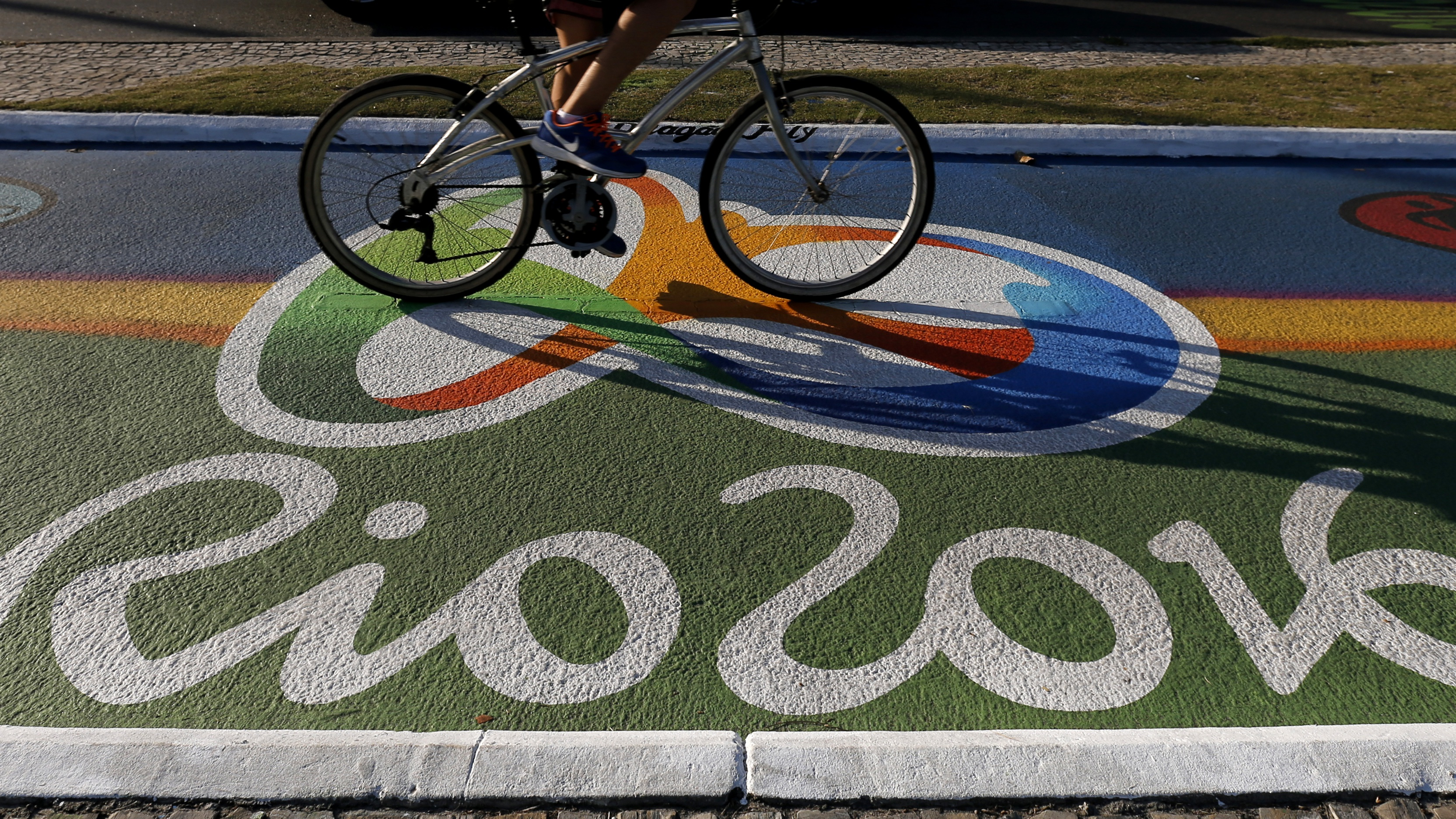 A woman rides her bicycle as she passes over a newly-painted bicyle lane ahead of the Rio 2016 Olympic games near Barra da Tijuca beach in Rio de Janeiro, Brazil, July 27, 2016. REUTERS/Sergio Moraes