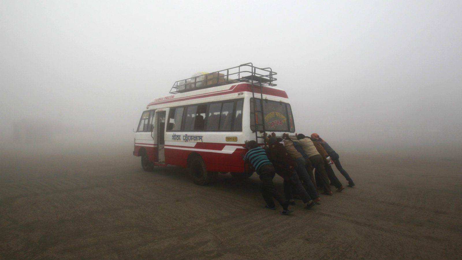 Passengers push their bus to start it amid dense fog on a cold winter morning on the outskirts of Agartala, capital of India's northeastern state of Tripura, January 7, 2014. Cold wave conditions continue across most parts of north India with temperatures at most places remaining below normal, local media reported.
