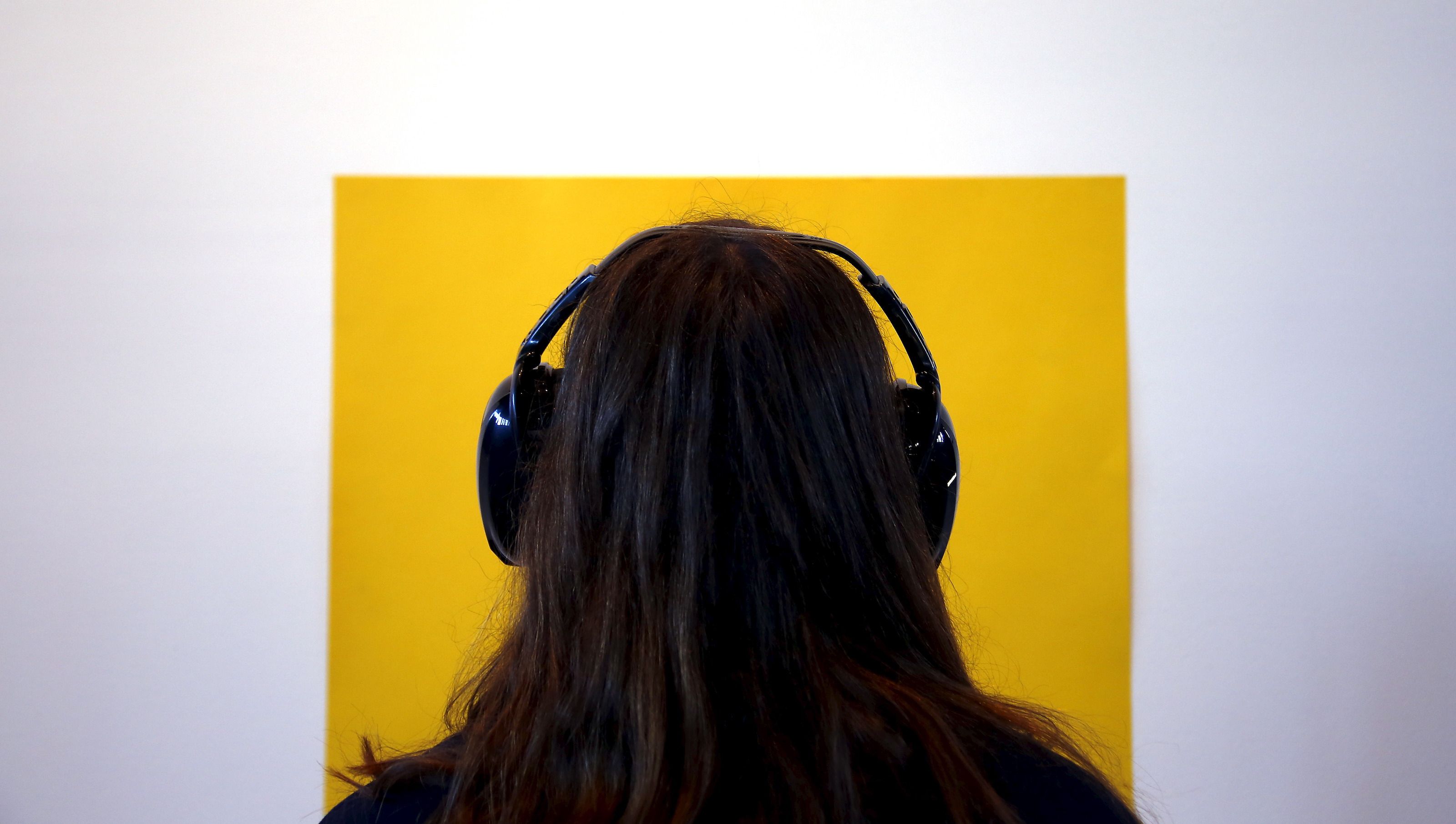 "A visitor wearing noise-cancelling headphones looks at a yellow piece of paper stuck to a wall as she tours the latest project by performance artist Marina Abramovic titled ""Marina Abramovic: In Residence"" on display as part of a public art project in Sydney, Australia June 23, 2015. The project involves visitors being a part of the artwork, making them perform exercises, complete tasks and resting while wearing noise-cancelling headphones. REUTERS/David Gray ATTENTION EDITORS - FOR EDITORIAL USE ONLY. NOT FOR SALE FOR MARKETING OR ADVERTISING CAMPAIGNS.  - RTX1HNZN"