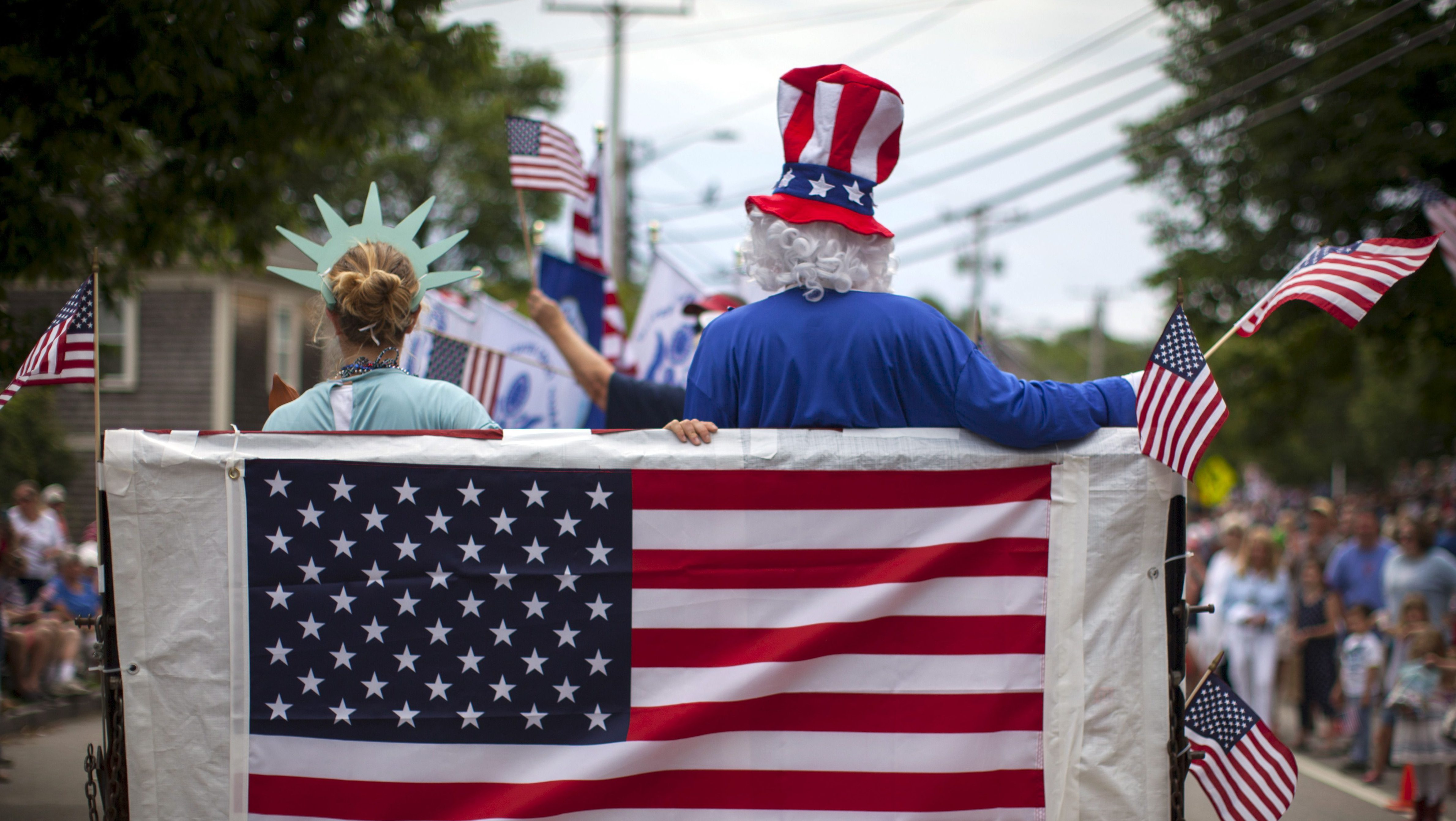 People in costumes ride on a float through Barnstable Village on Cape Cod during the annual 4th of July Parade in Barnstable