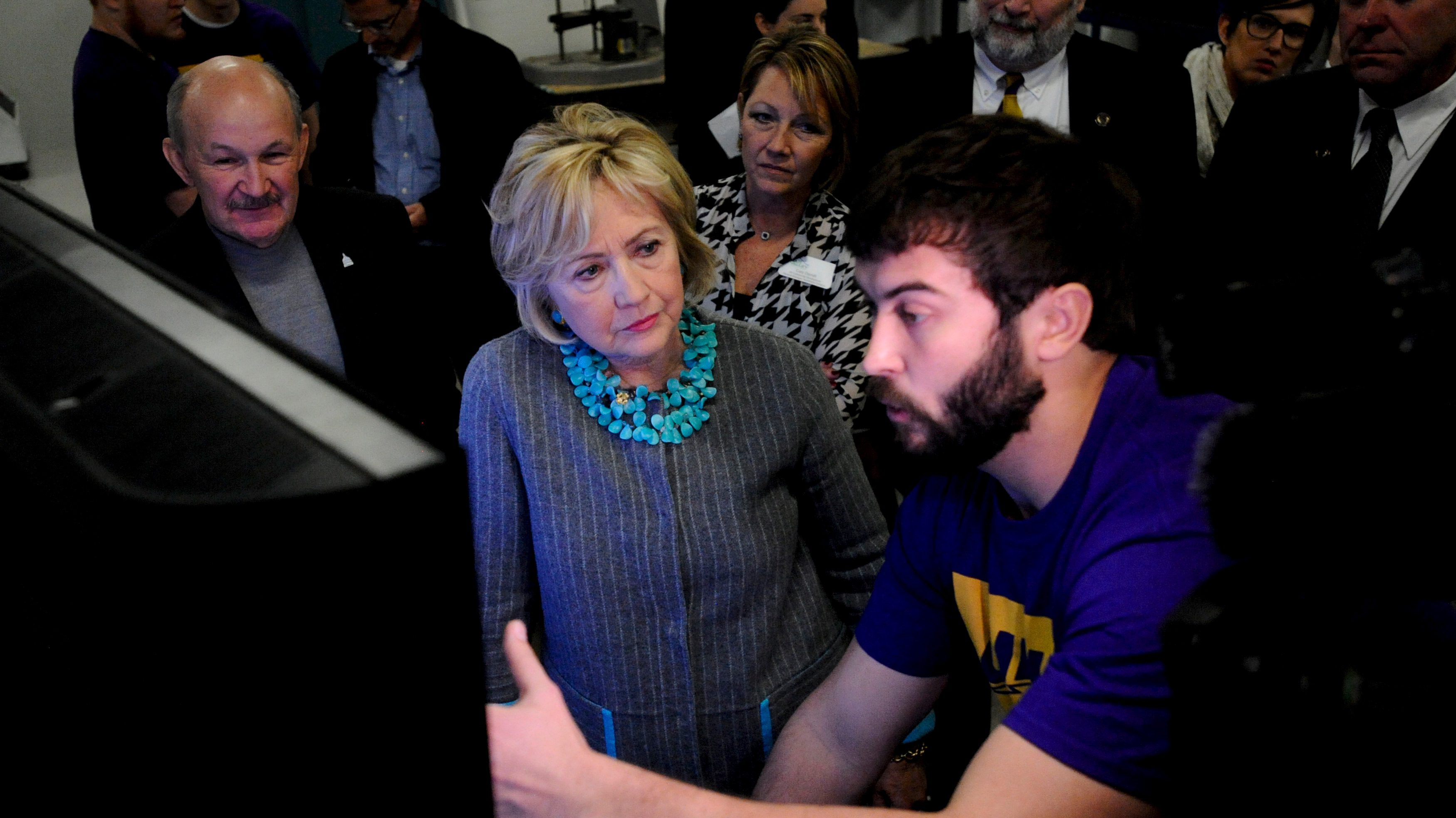 U.S. Democratic presidential candidate Hillary Clinton (C) is shown the designs that are fed into the 3-D printer at Cedar Valley TechWorks in Waterloo, Iowa December 9, 2015.