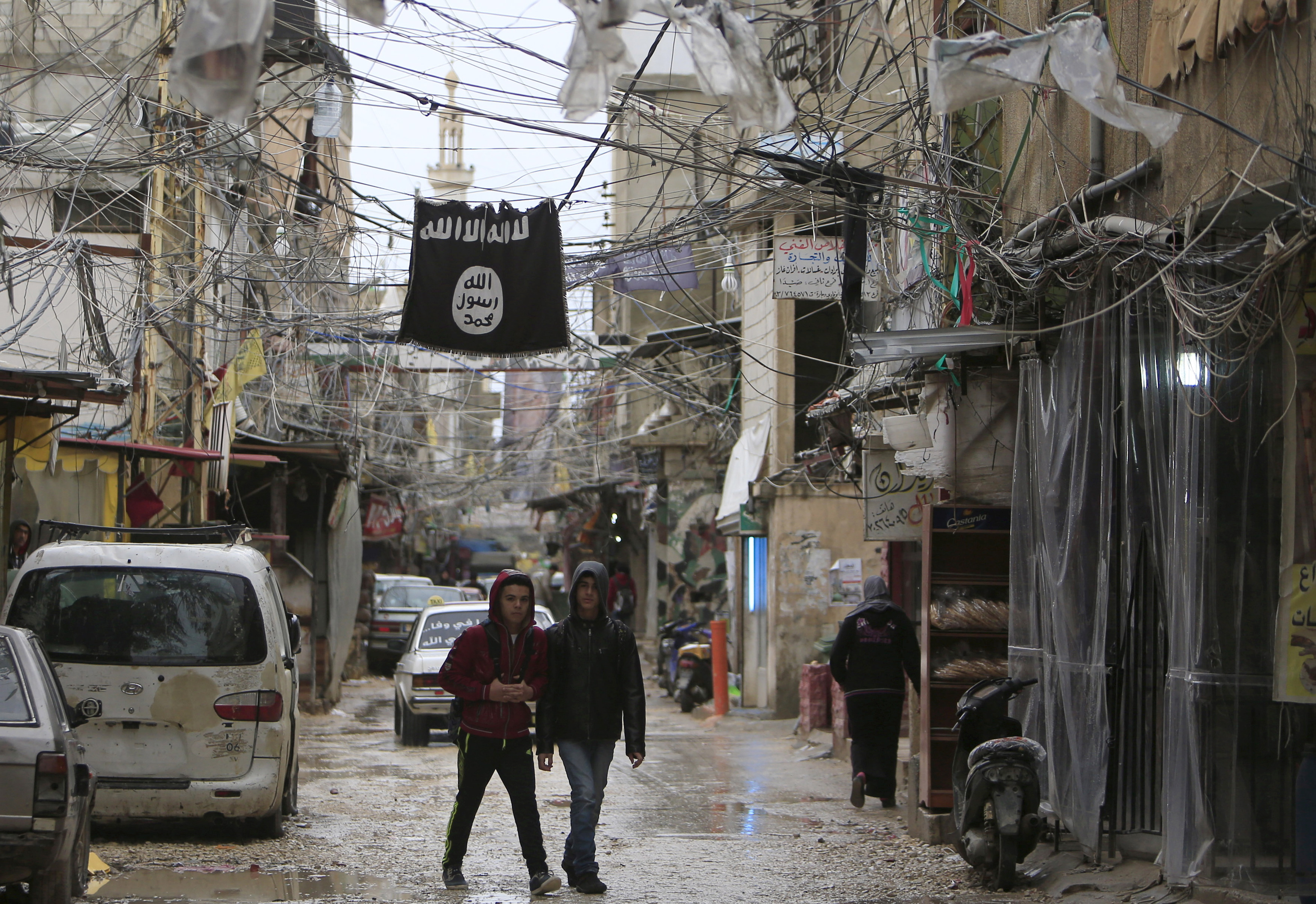 Youth walk under an Islamic State flag in Ain al-Hilweh Palestinian refugee camp, near the port-city of Sidon