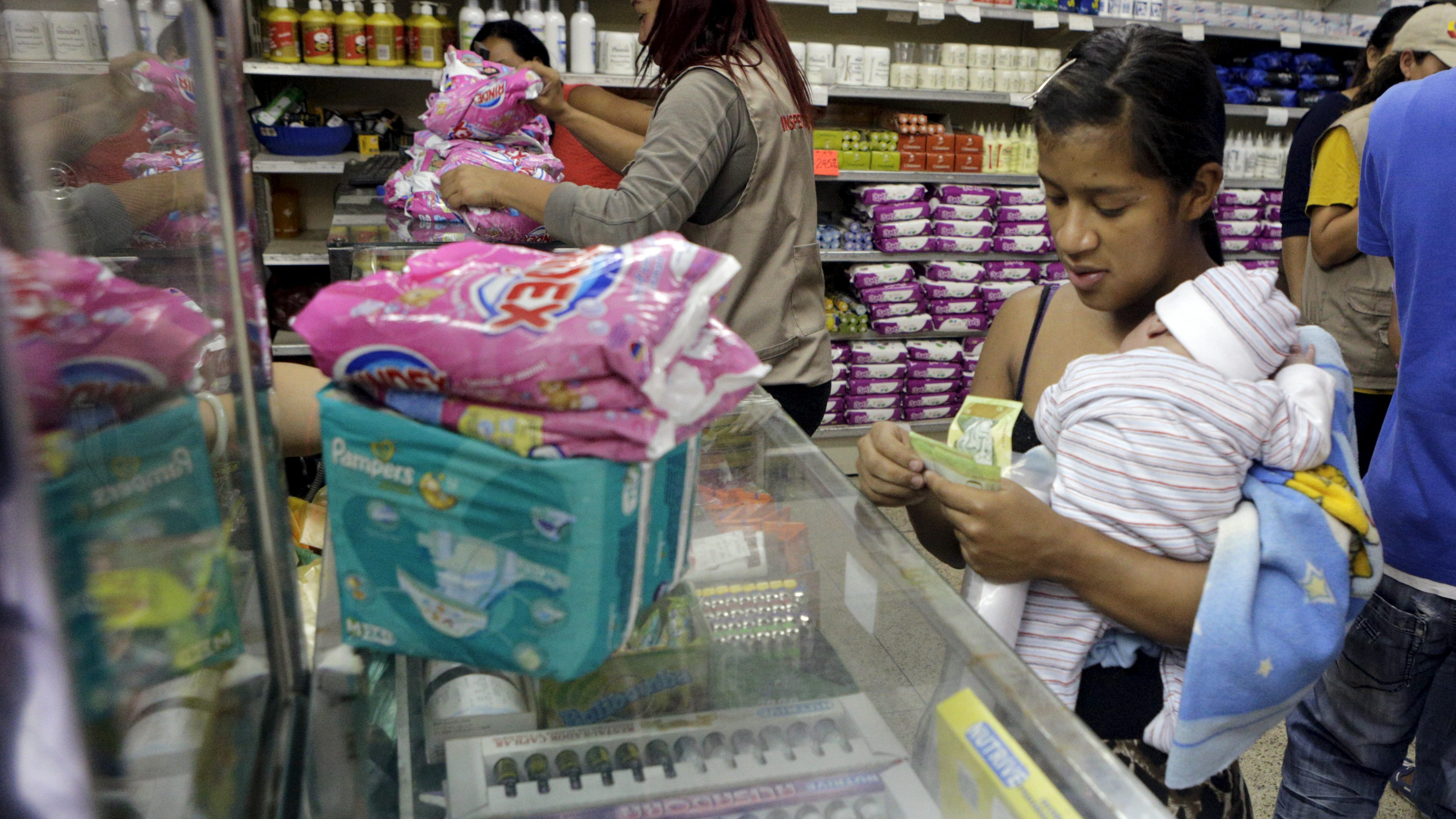 A woman carrying her 18-day-old baby counts bolivar notes as she buys diapers and laundry soap at a supermarket in Caracas