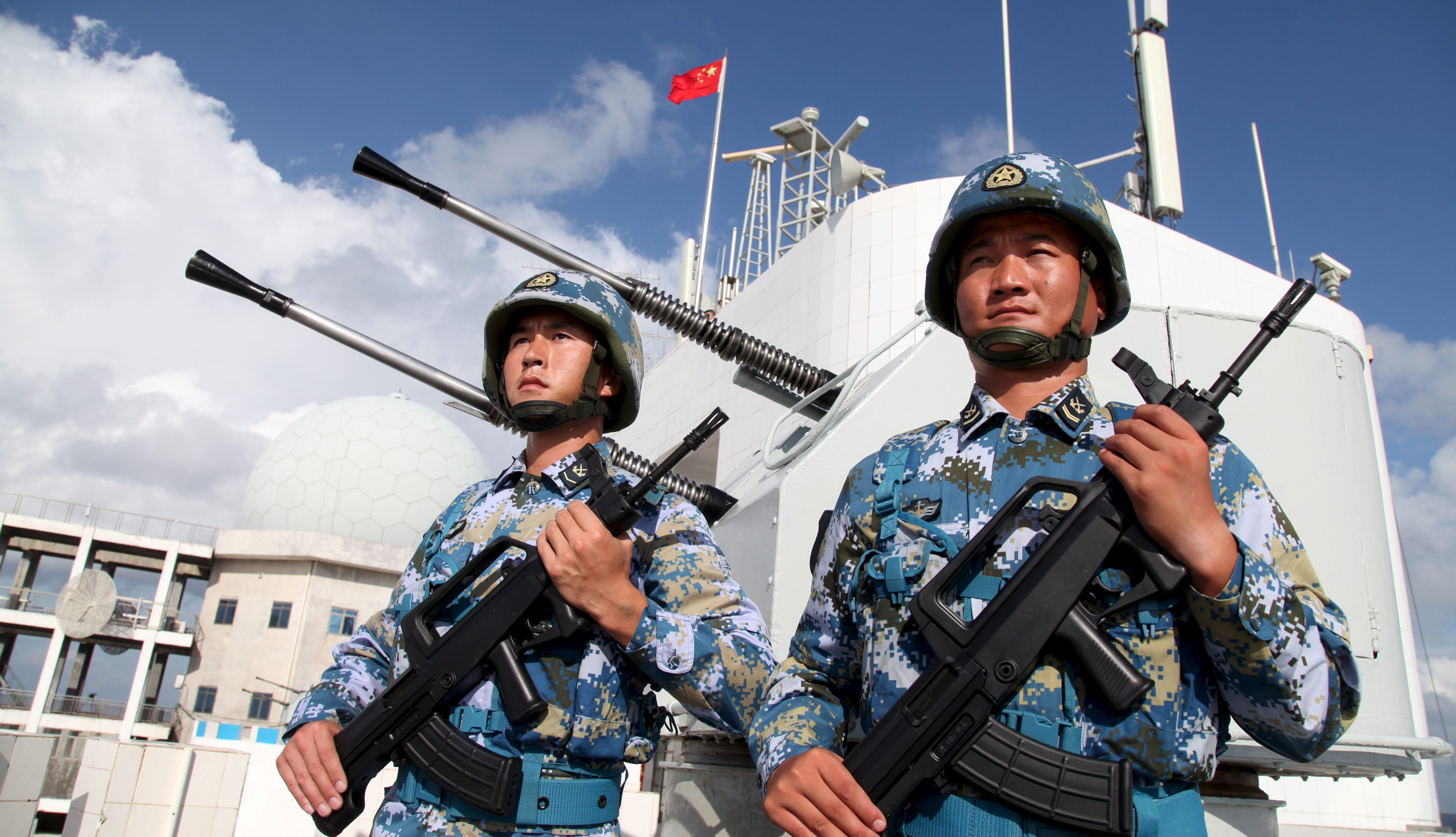 Soldiers of China's People's Liberation Army (PLA) Navy stand guard in the Spratly Islands, known in China as the Nansha Islands, February 10, 2016.