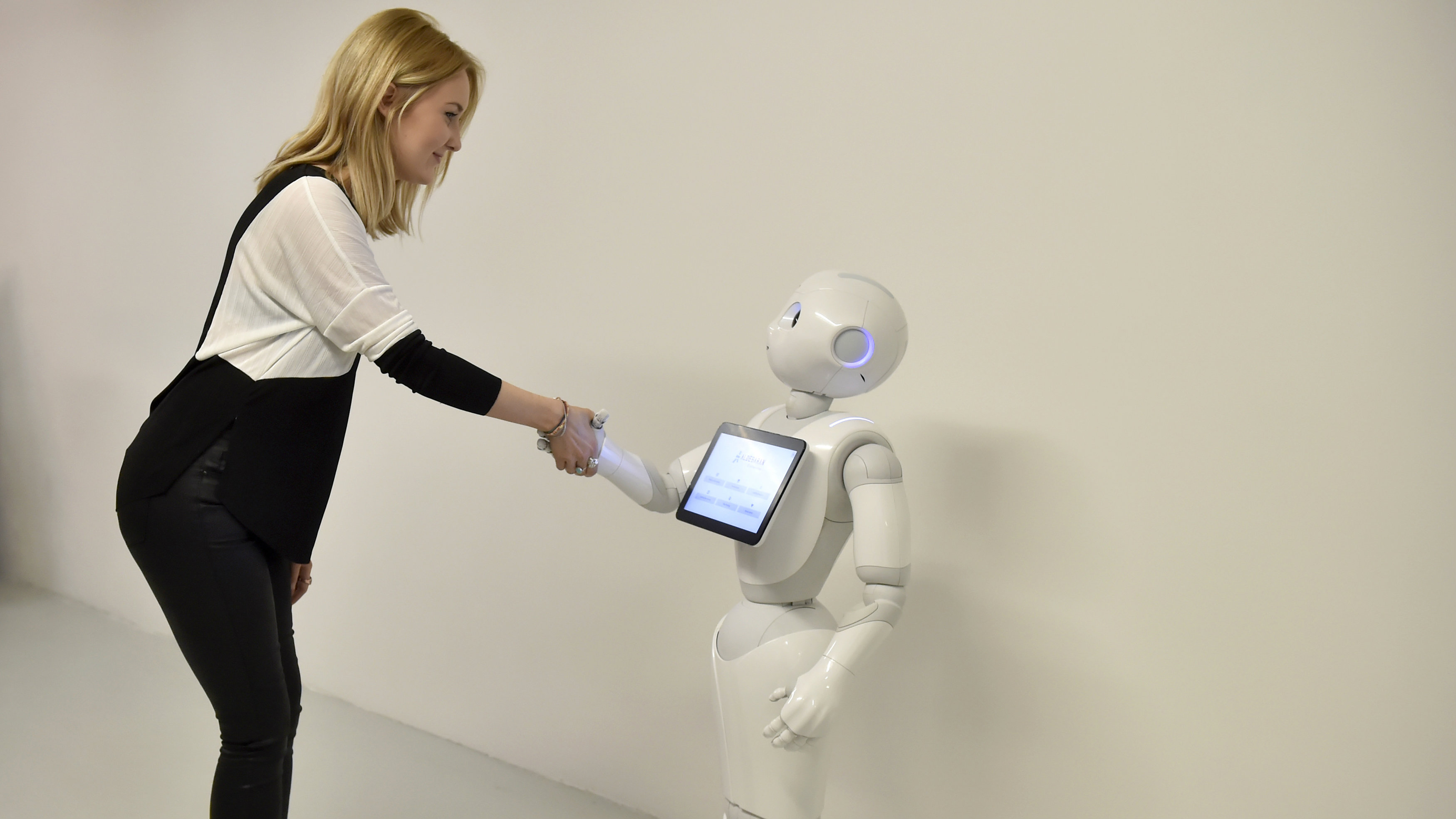 A press officer poses with 'Pepper' the Humanoid Robot at the 'World of Me: Store of the near future installation' in London, Britain, April 13, 2016. The robot is the first humanoid robot capable of recognising the principal human emotions and adapting his behaviour accordingly.