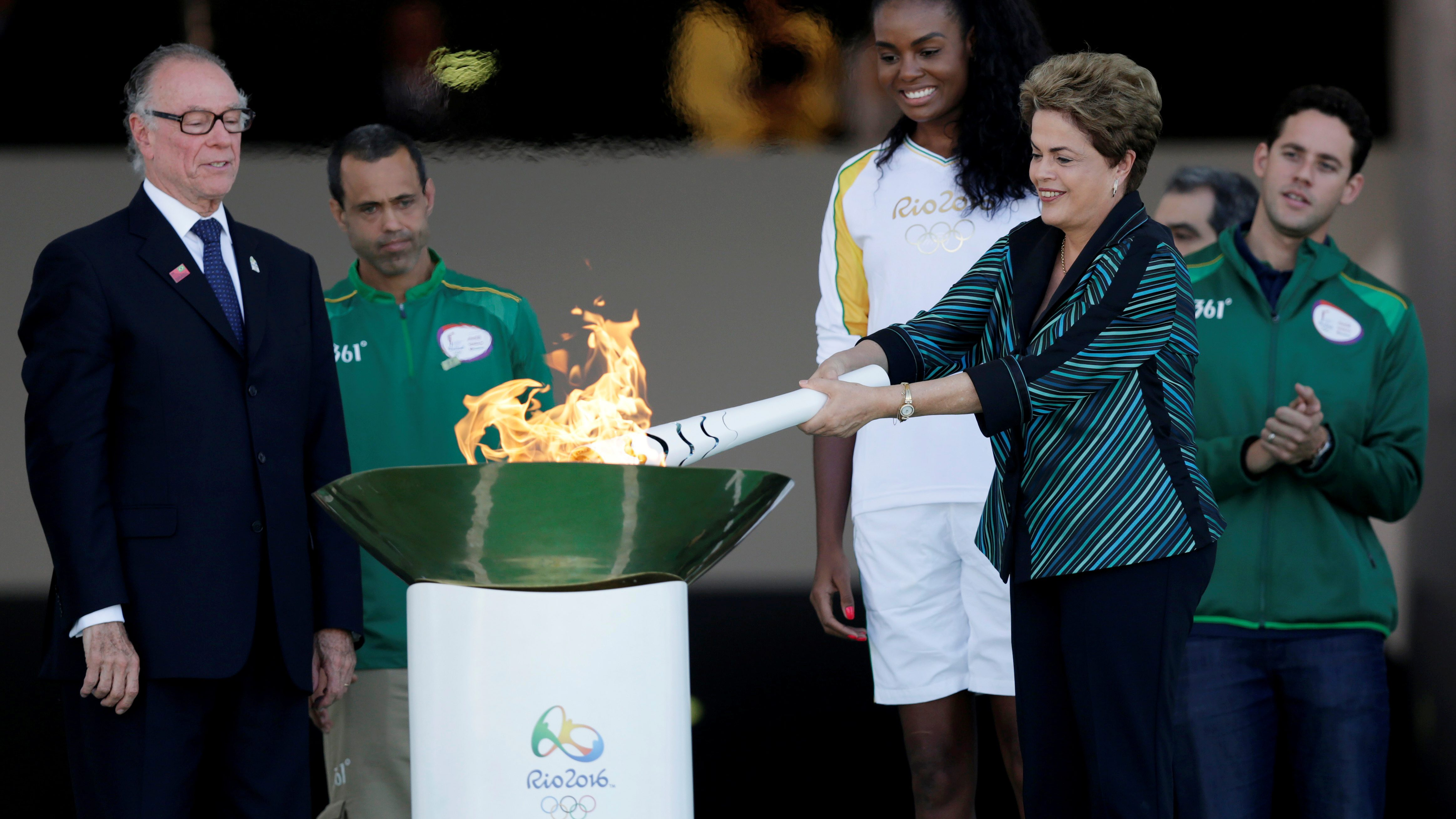 Brazil's President Rousseff lights a cauldron with the Olympic Flame next to Fabiana Claudino, captain of the Brazilian volleyball team, during the Olympic Flame torch relay in Brasilia