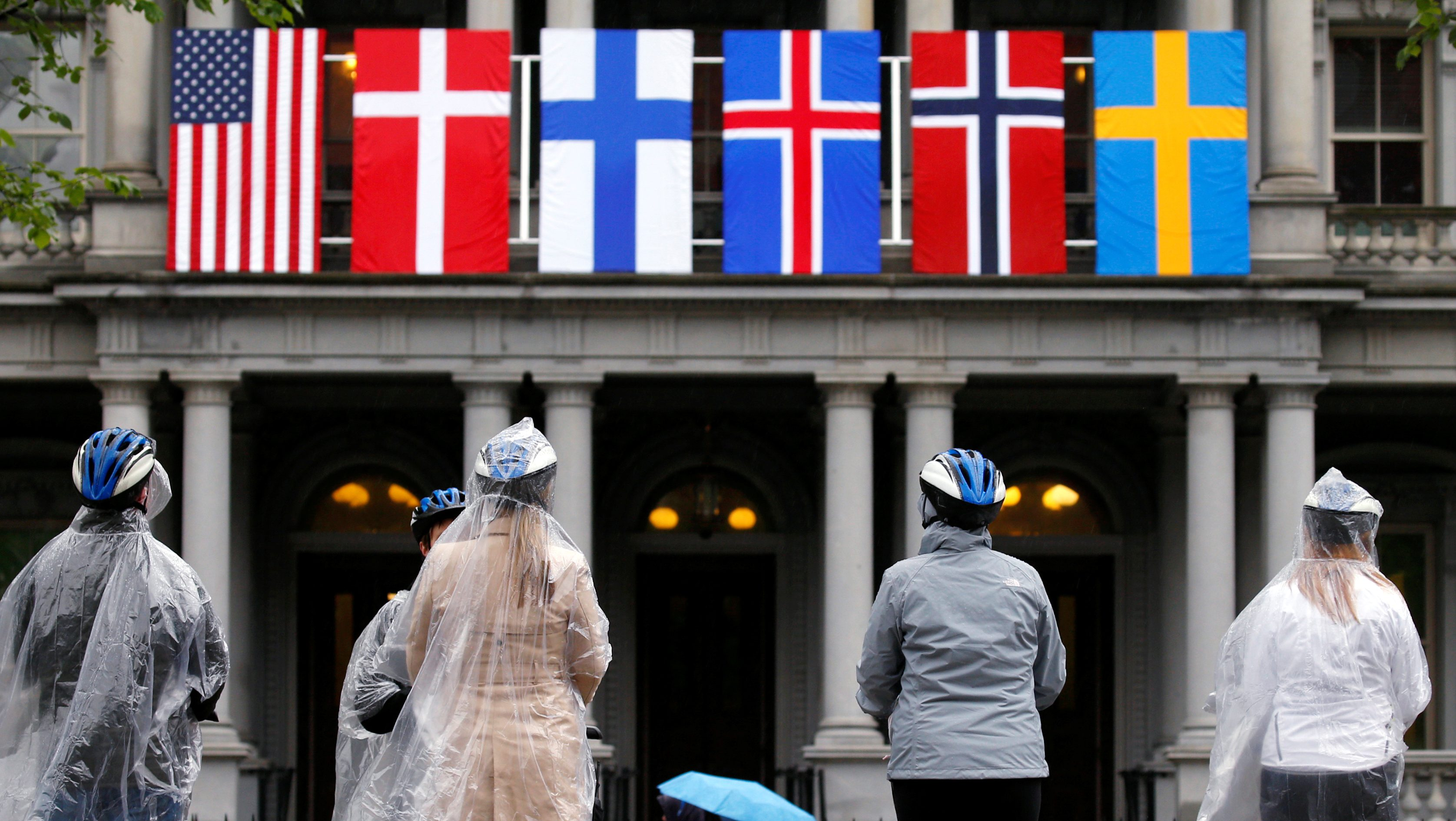 A segway tour stops in front of flags of the Nordic nations hanging from the Eisenhower Executive Office Building beside the White House in Washington, May 11, 2016. On Friday, U.S. President Barack Obama will host the leaders of Denmark, Finland, Iceland, Norway and Sweden for a U.S.-Nordic Leaders Summit. REUTERS/Kevin Lamarque - RTX2DW5U