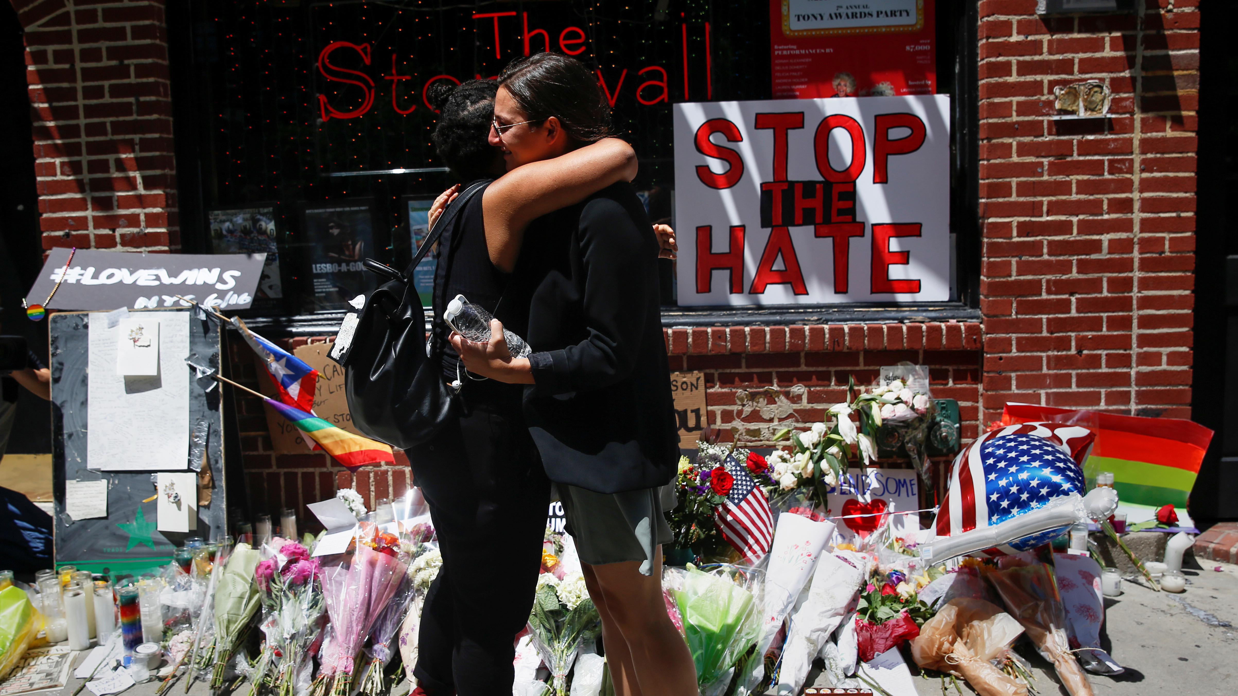 Matti Mejia and Shaina Roberts embrace after laying flowers at memorial outside The Stonewall Inn remembering the victims of the Orlando massacre in New York
