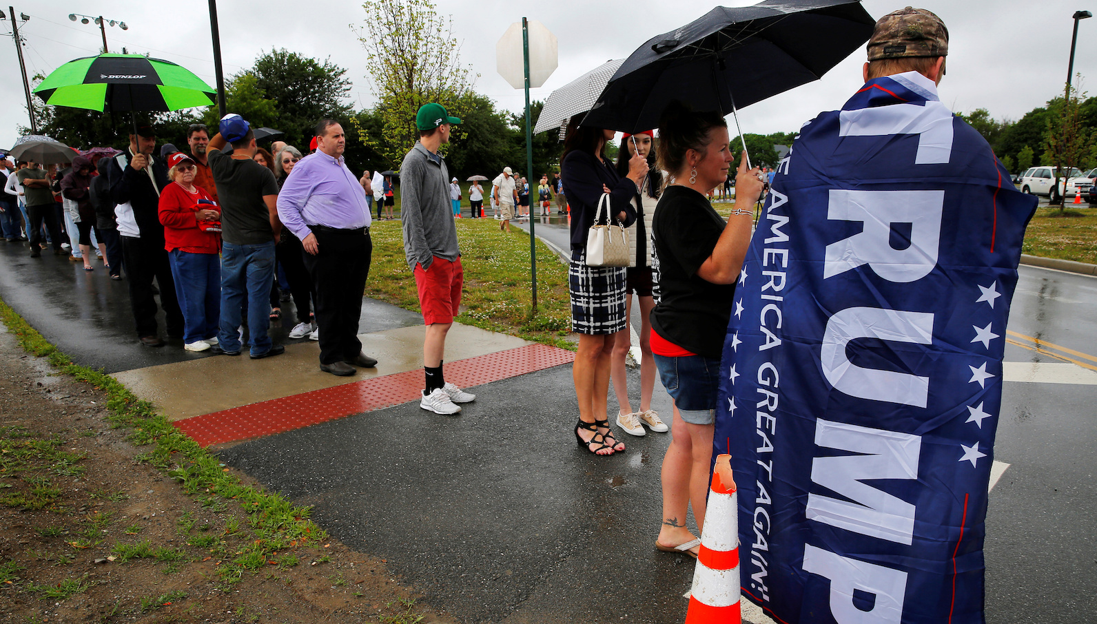Alex Fraser wears a campaign banner as a cape while waiting in line for a campaign rally with U.S. Republican presidential candidate Donald Trump in Bangor, Maine, U.S. June 29, 2016. REUTERS/Brian Snyder - RTX2IX8U