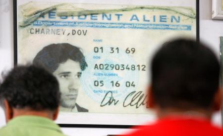 Workers queue for lunch in front of a poster-size photo of the first alien resident card of company Chief Executive Dov Charney at the American Apparel factory in downtown Los Angeles, October 17, 2008. While immigration is almost a non-issue in the U.S. presidential campaign, American Apparel, the biggest garment manufacturer in the country, is doing its best to keep the debate alive, saying legalizing foreign workers is good for business. To match feature USA-IMMIGRATION/AMERICANAPPAREL REUTERS/Lucy Nicholson (UNITED STATES) - RTX9Z9E