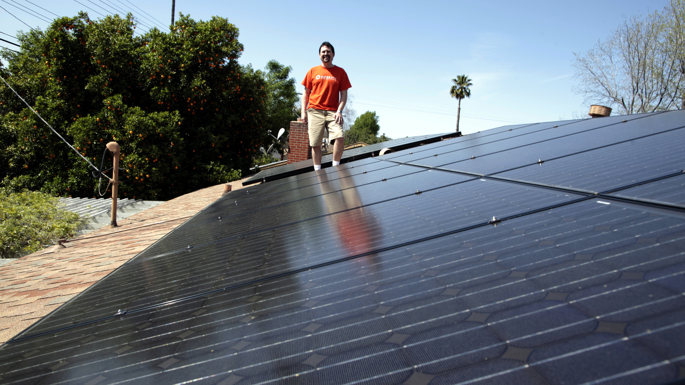 Mike Jones stands next to solar panels on the roof of his home in Los Angeles, California March 18, 2011. Jones leased 22 solar panels from solar electric system company Sungevity. The panels would have cost him $13,000, but the 20-year lease cost $4,000. The first month after the panels were installed Jones' electricity bill went down from $160 to $11. (UNITED STATES - Tags: ENVIRONMENT ENERGY)