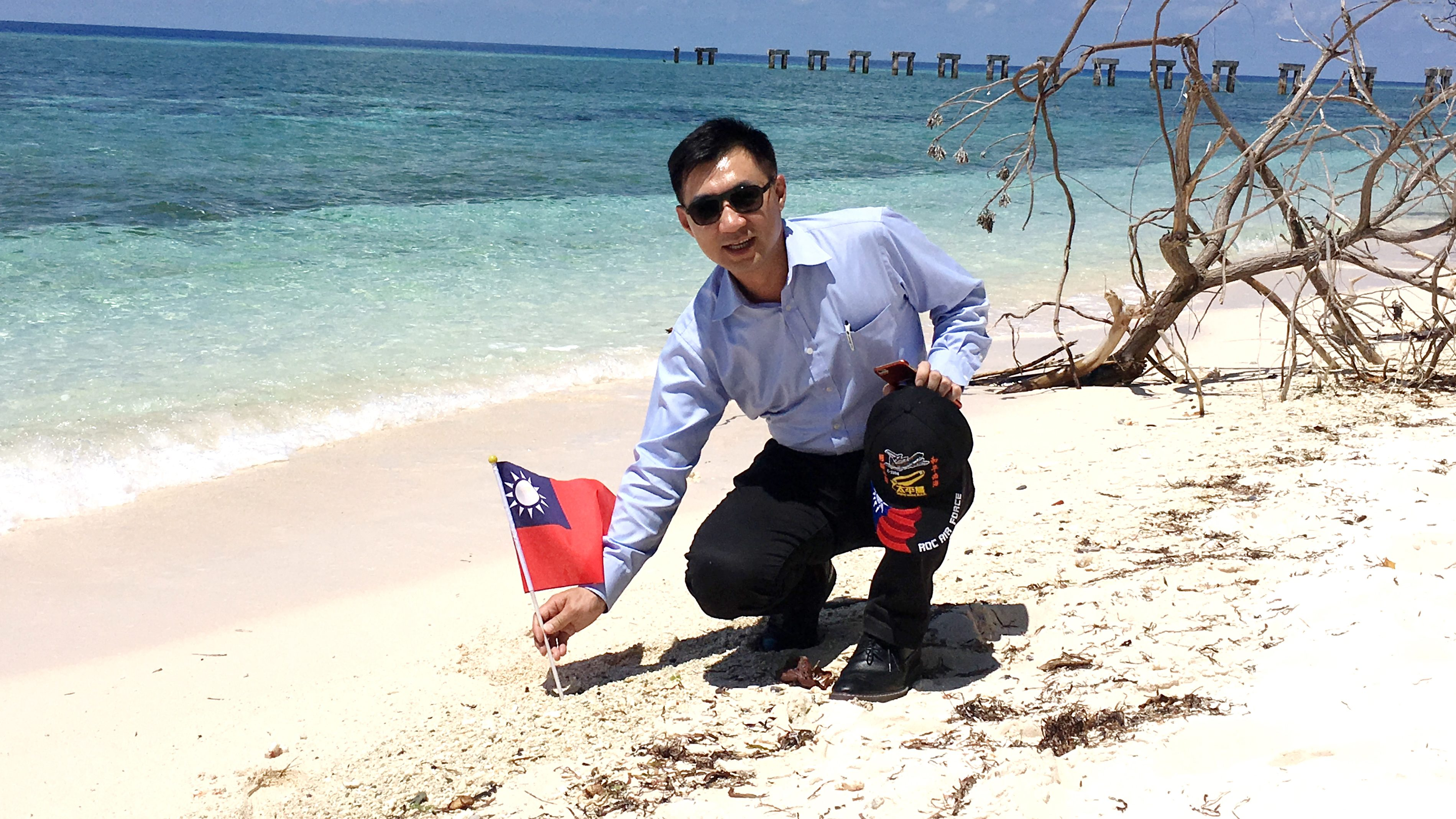 Taiwanese lawmaker Chiang Chi-chen plants the national flag on Taiping Island on July 20, 2016.