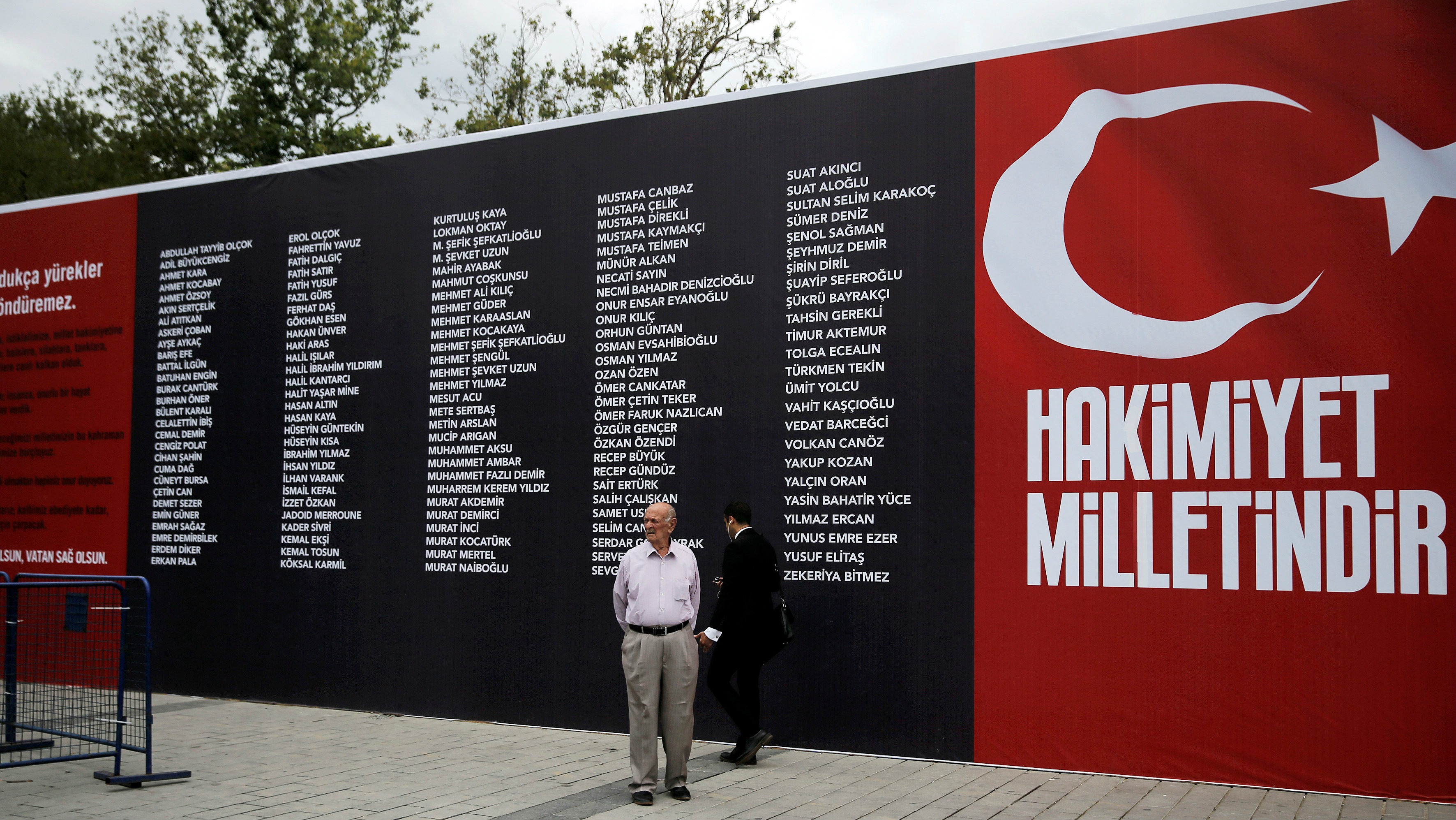 """A man stands in front of a banner reading the names of civilians and policemen who were killed while resisting the coup attempt, on Taksim square in Istanbul, Turkey, July 20, 2016. The slogan reads """"Sovereignty belongs to the nation"""