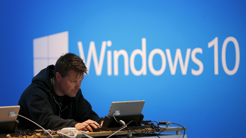 A man works on a laptop computer near a Windows 10 display at Microsoft Build in San Francisco, California April 29, 2015. REUTERS/Robert Galbraith