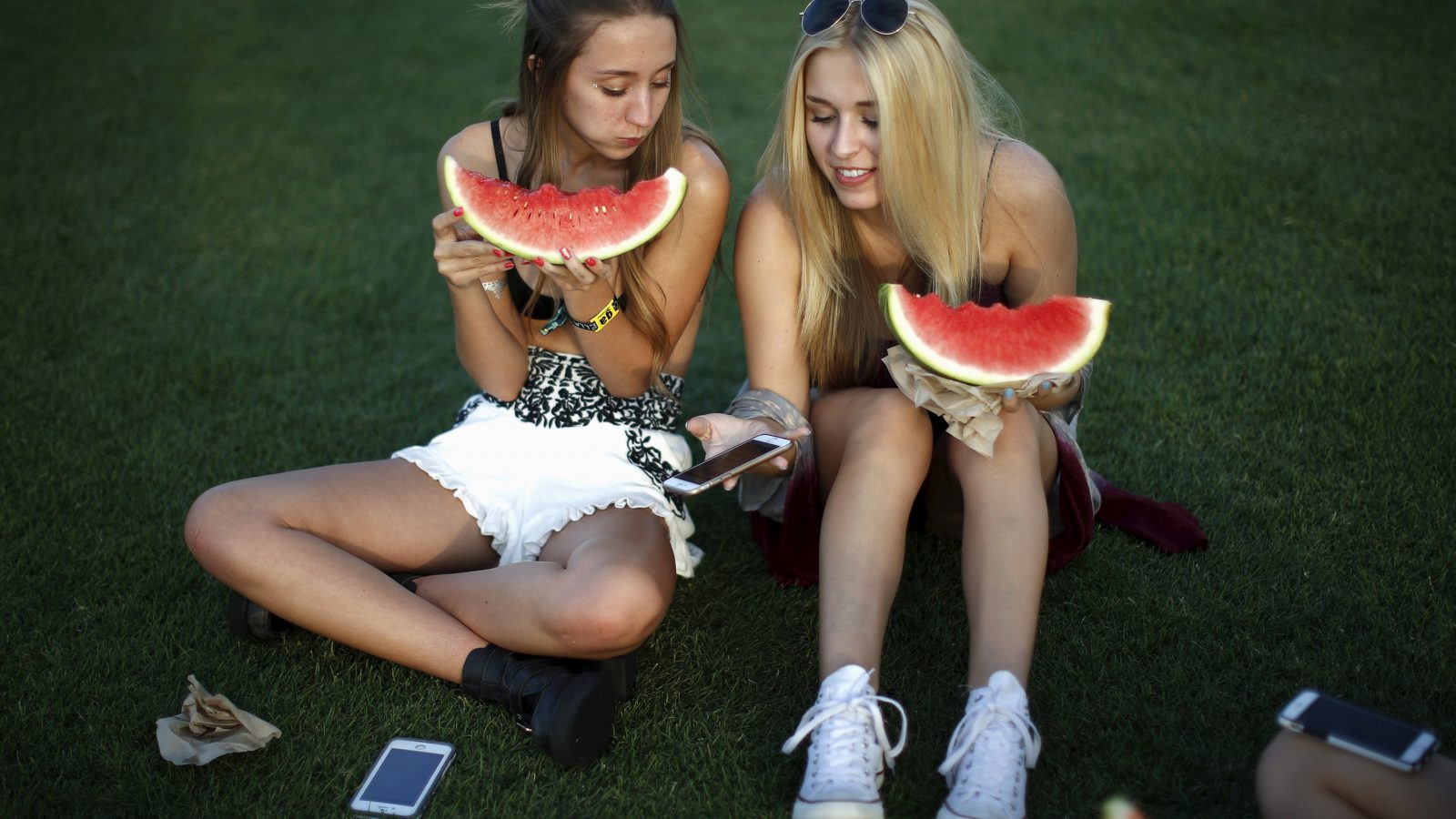 Women eat watermelons at the Coachella Valley Music and Arts Festival in Indio, California April 10, 2015. REUTERS/Lucy Nicholson - RTR4WW3U