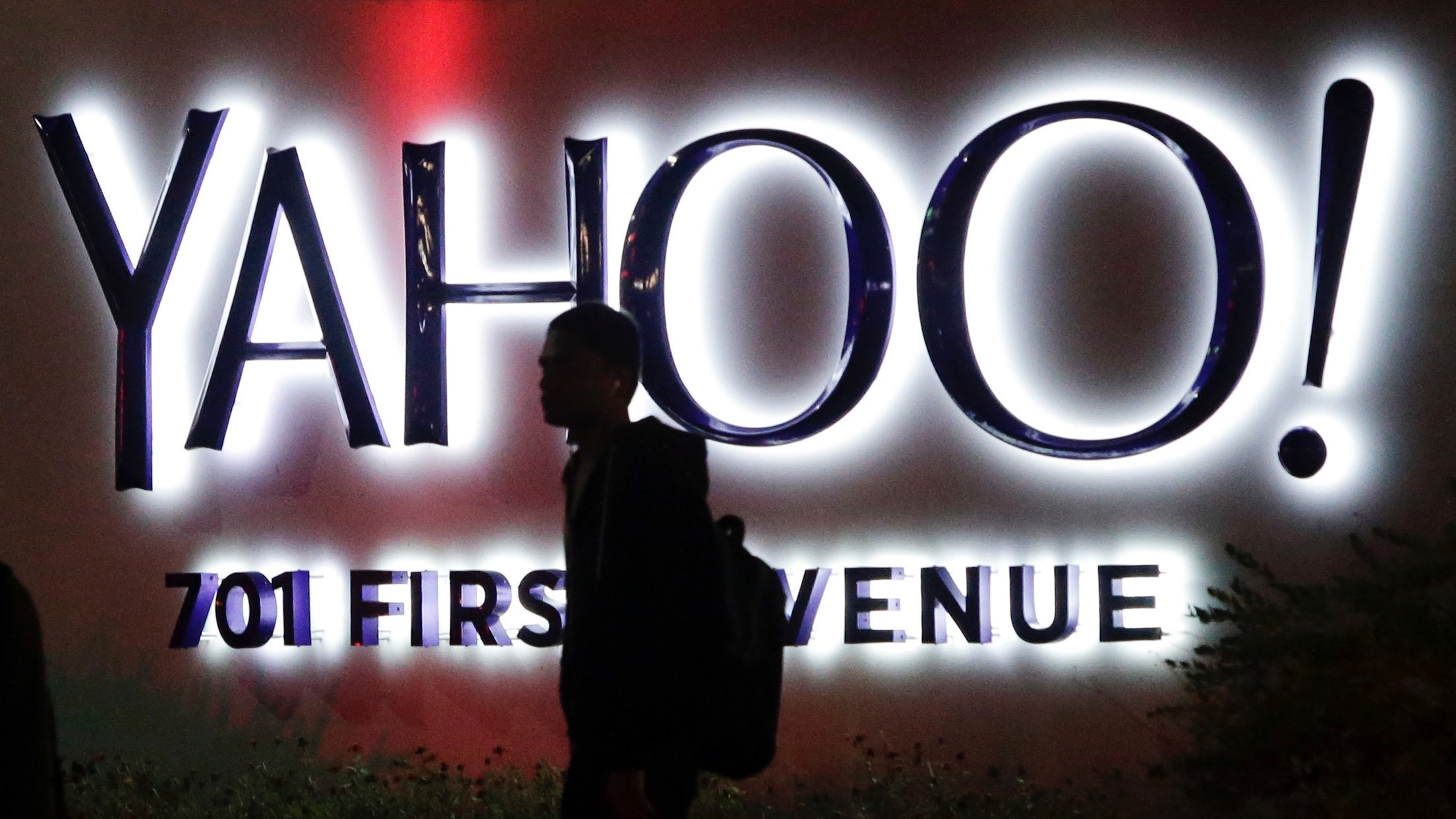 FILE - In this Nov. 5, 2014, file photo, a person walks in front of a Yahoo sign at the company's headquarters in Sunnyvale, Calif. Yahoo reported Tuesday, April 19, 2016, that after subtracting ad commissions, Yahoo's revenue fell 18 percent from the same time a year earlier, to $859 million. It's the largest decline in Yahoo's quarterly net revenue since the company hired Marissa Mayer as its CEO nearly four years ago. (AP Photo/Marcio Jose Sanchez, File)