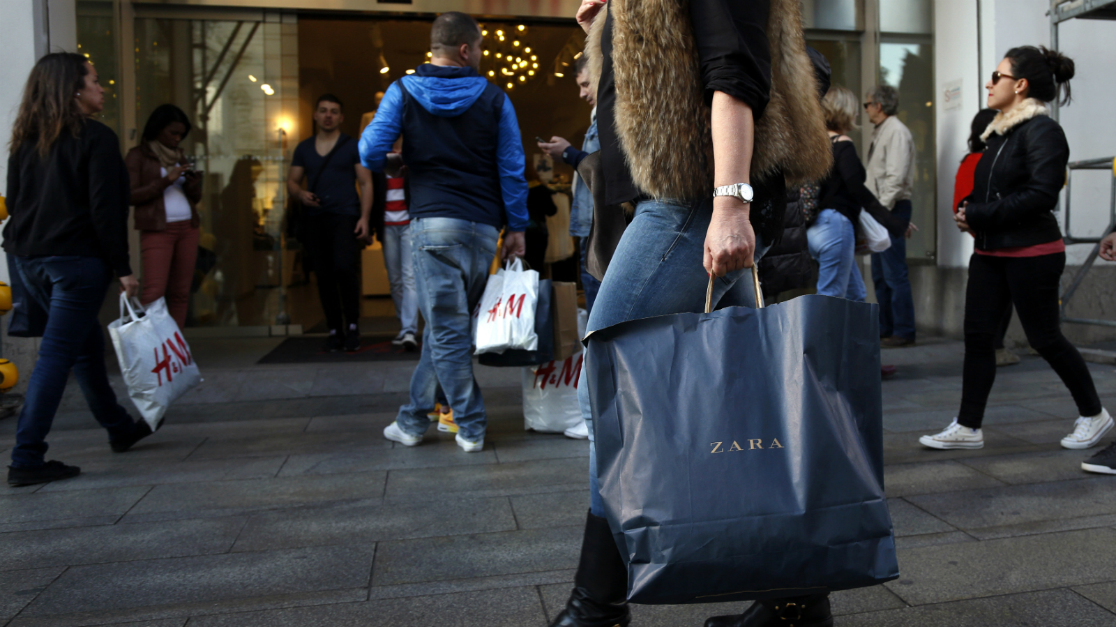 A woman carrying a Zara shopping bag walks past people holding H&M shopping bags outside an H&M store in central Madrid March 13, 2015. The families behind Zara-owner Inditex and H&M will need to fend off fast-moving competitors if they are to replicate online the winning formulae that made them the world's top two fashion retailers. Picture taken March 13, 2015.