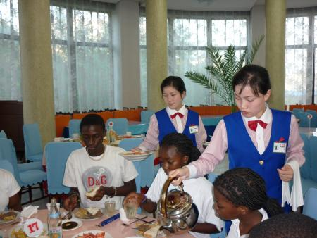 North Korean students serve meals to the other children.