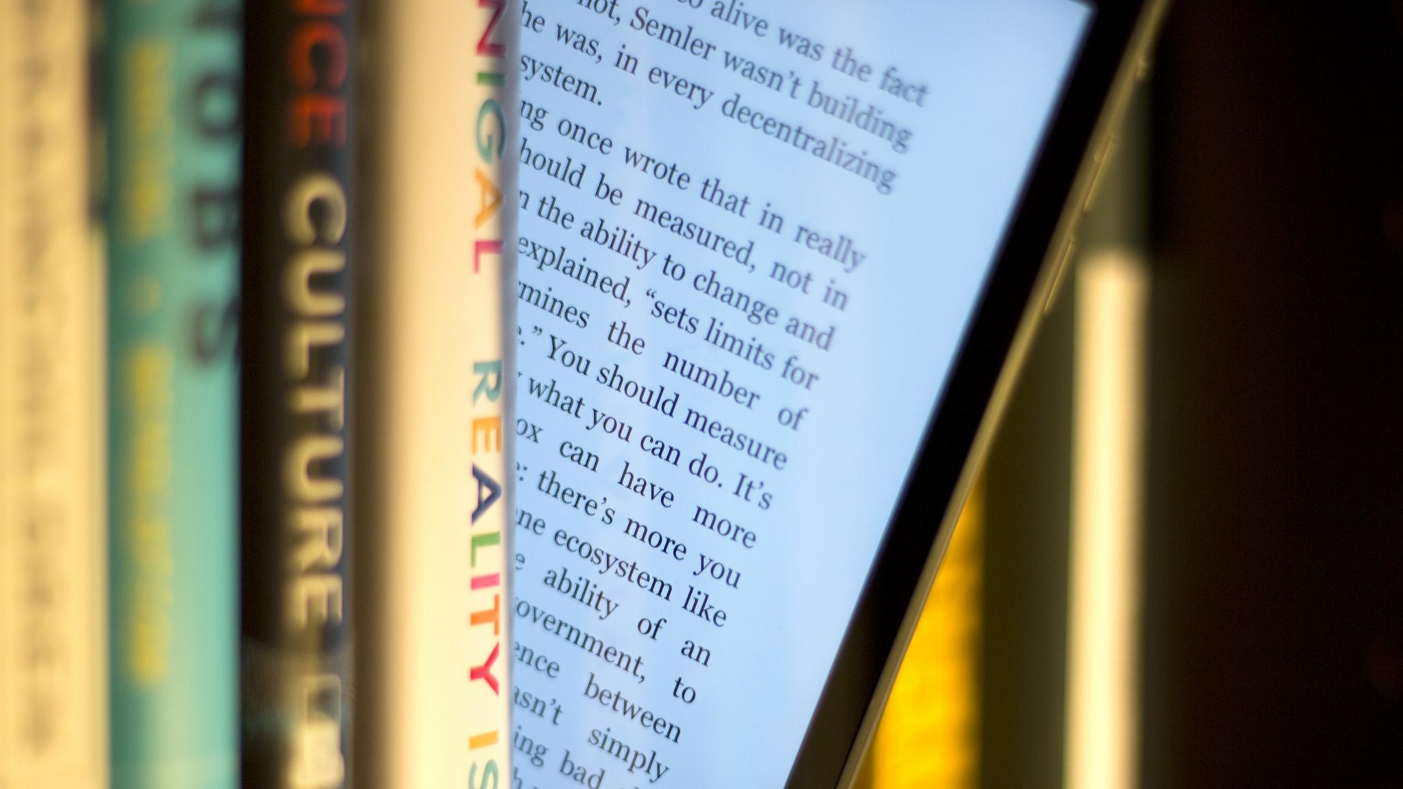 An ebook reader sticks out from a shelf full of books.