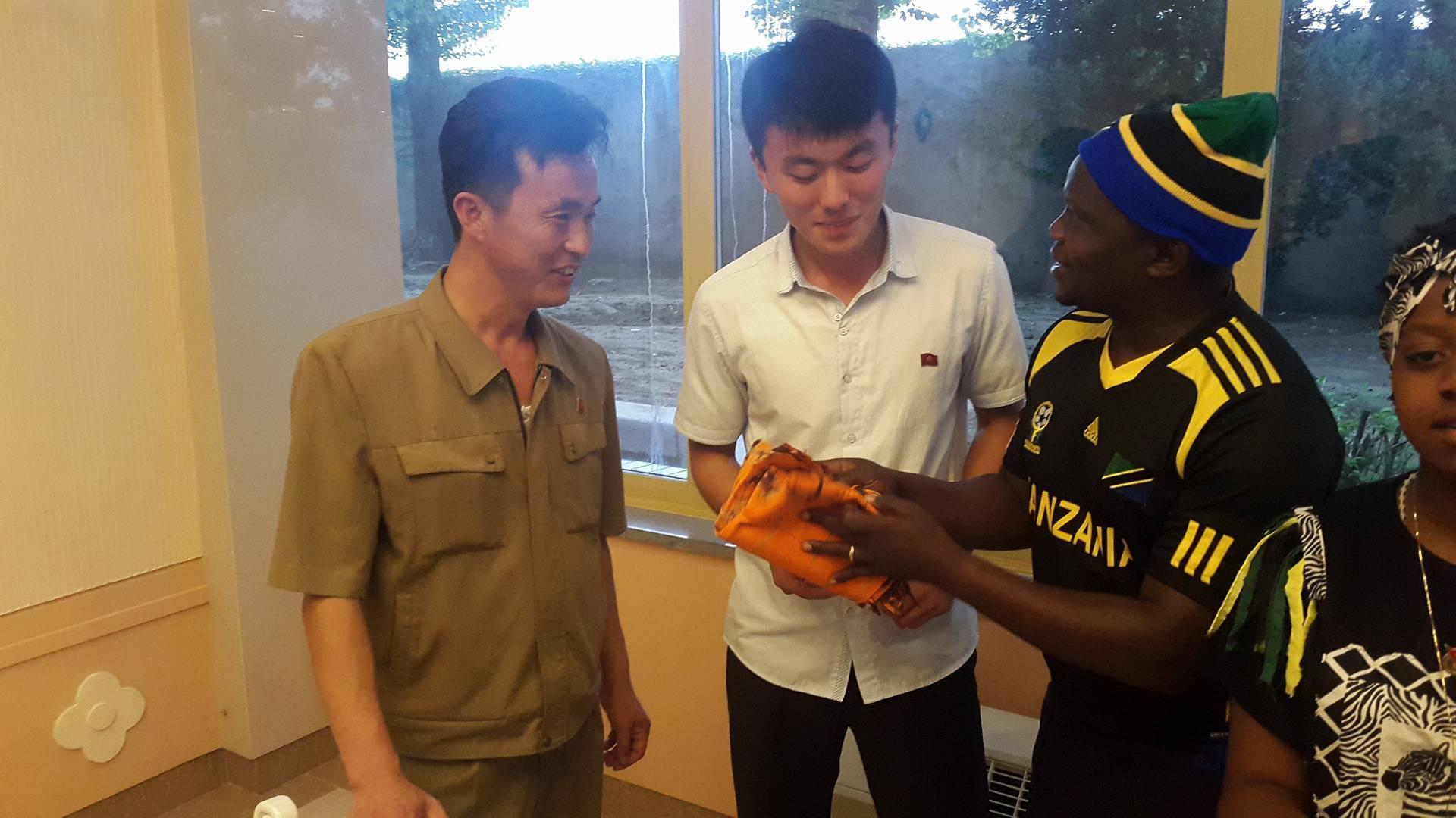 A Tanzanian student gives his North Korean hosts a gift.