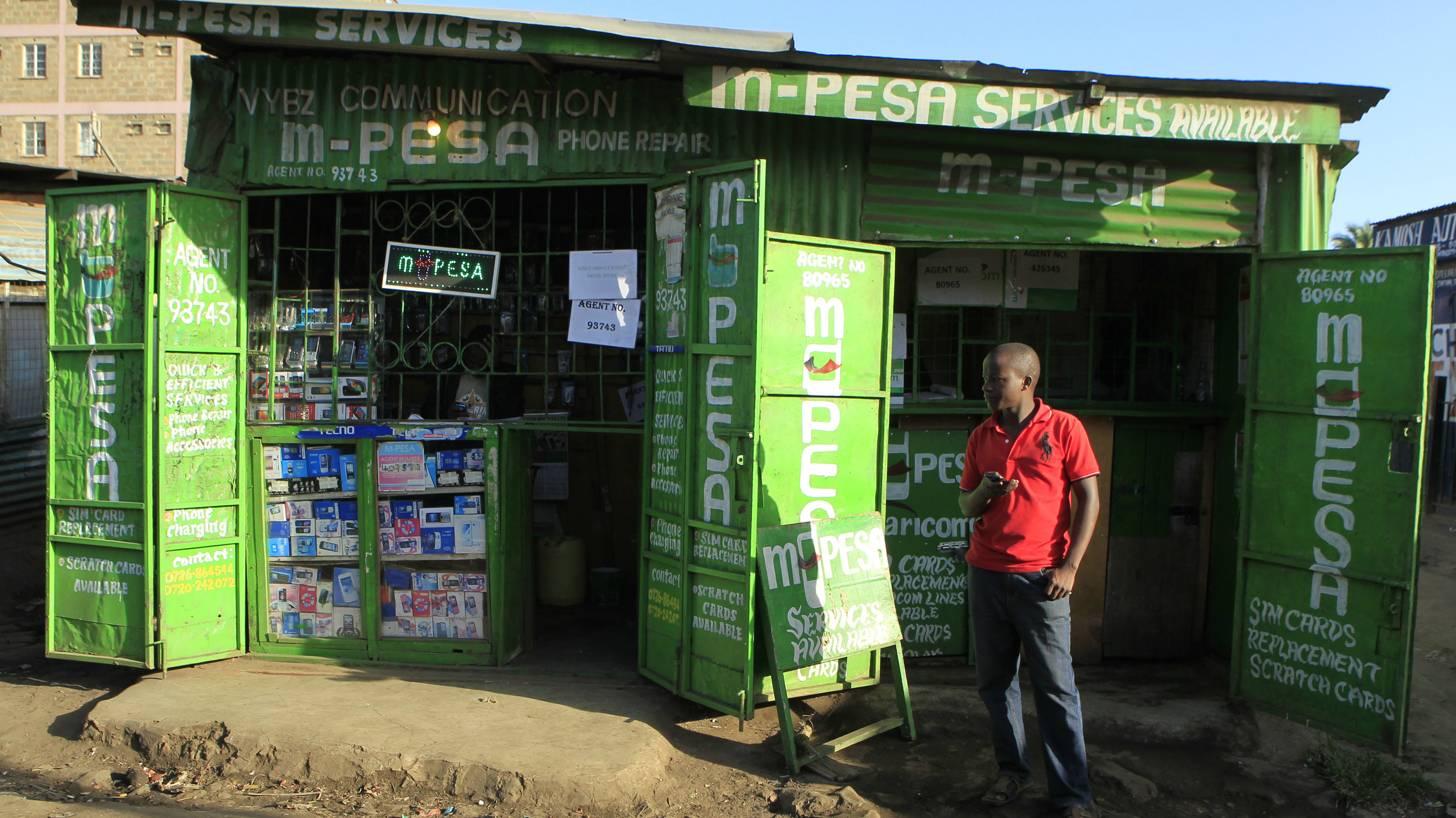 A man waits for M-Pesa customers at his shop in Kibera in Kenya's capital Nairobi December 31, 2014.
